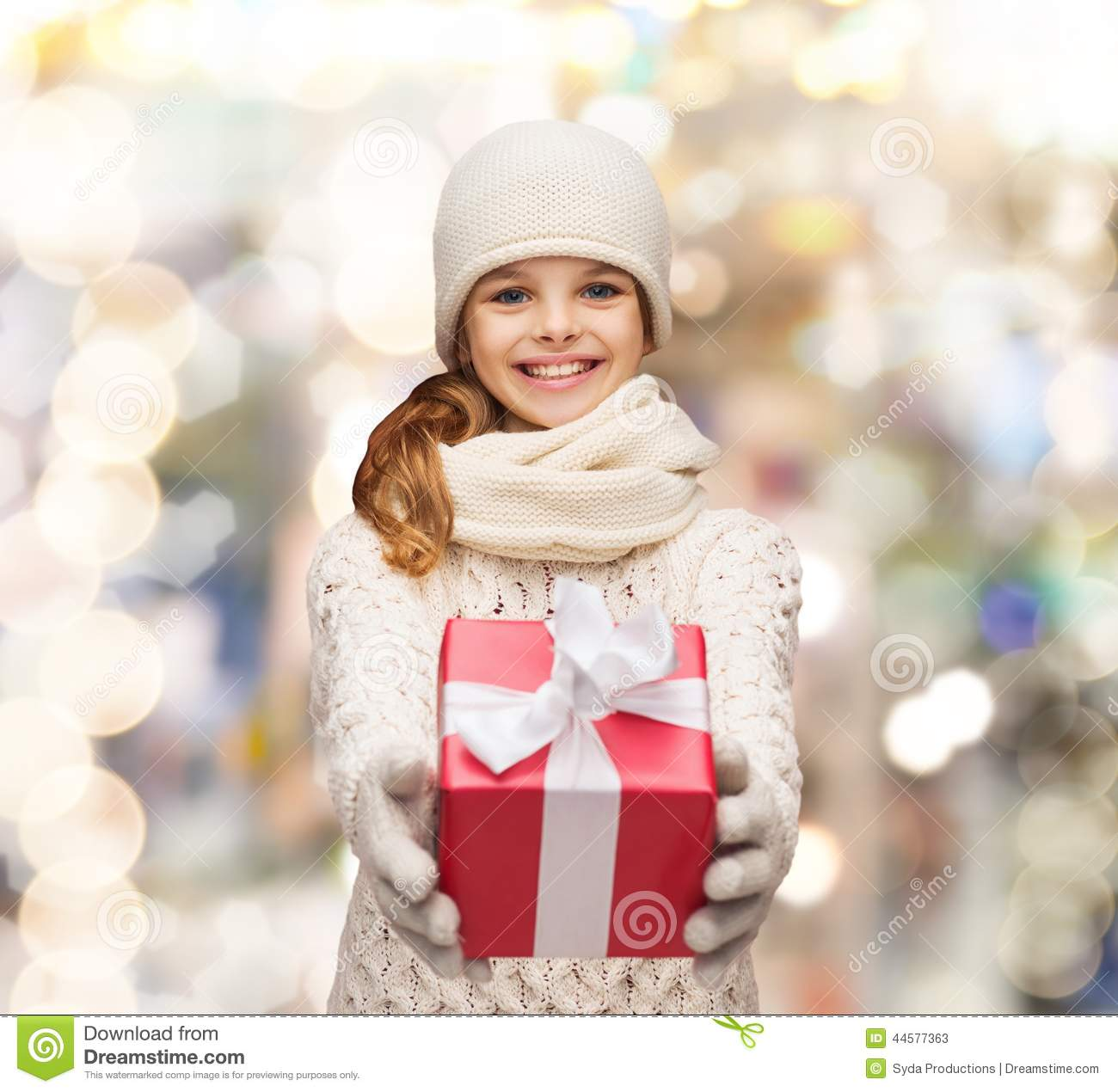 Dreaming girl in winter clothes with gift box