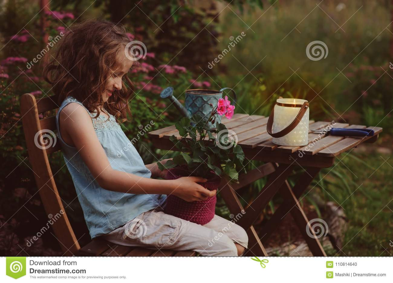dreamy romantic kid girl relaxing in evening summer garden