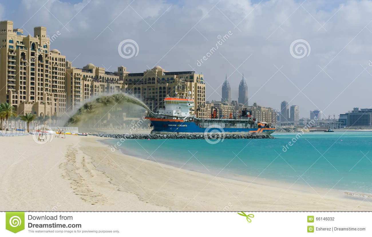 A dredger pumps sand to form a palm shaped island for Dubai hotels near beach