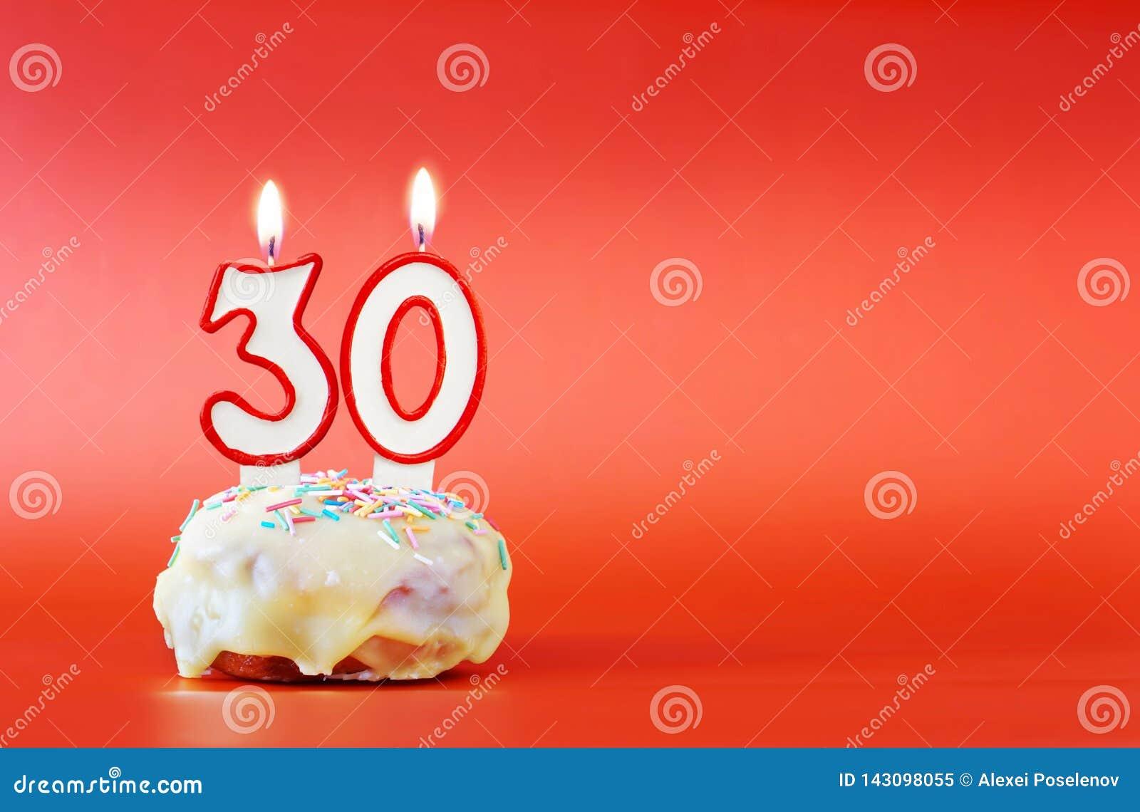 Dreißig Jahre Geburtstag Kleiner Kuchen mit weißer brennender Kerze in Form von Nr. 30