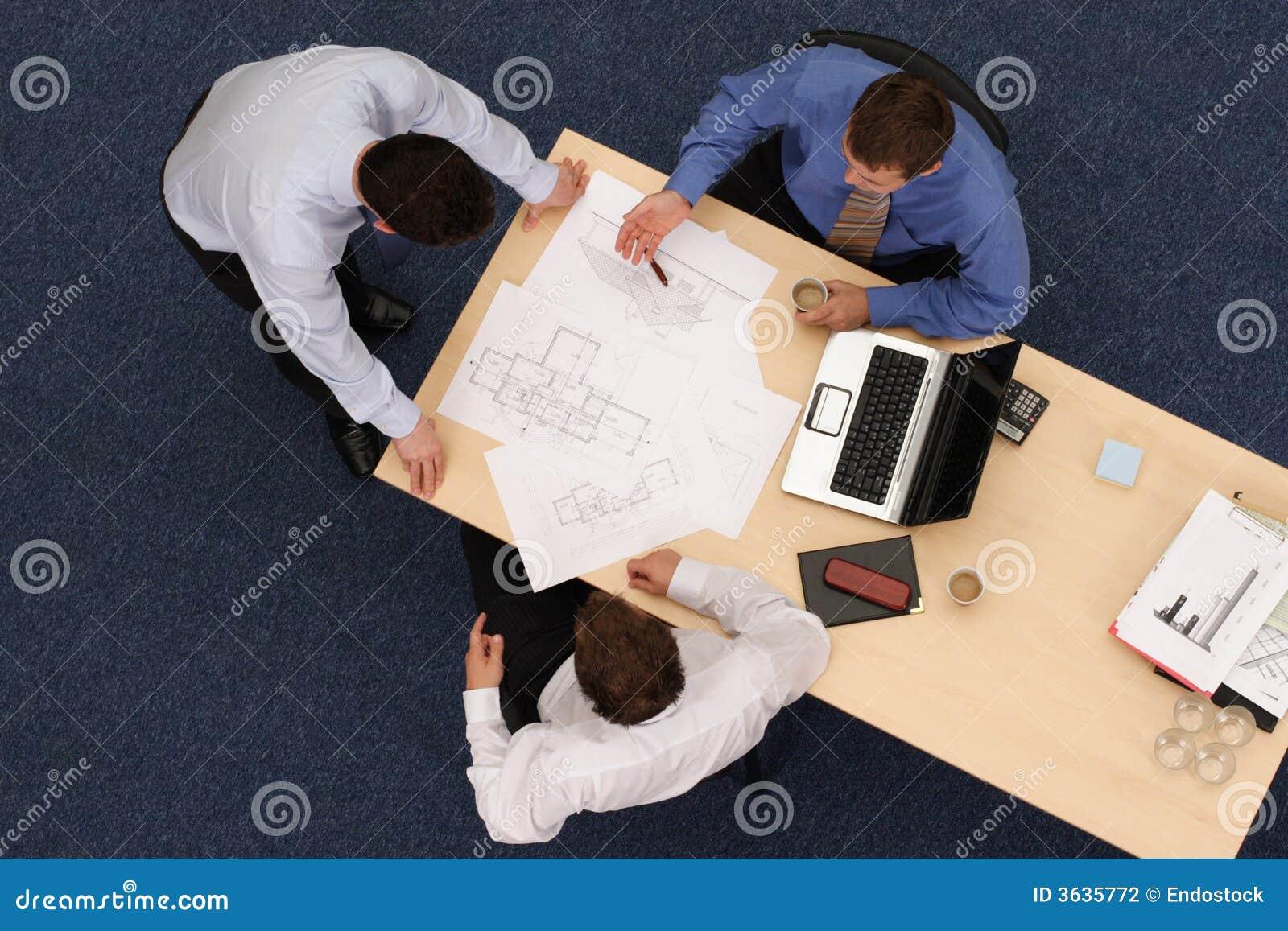 Drei ArbeitsGeschäftsleute über Blaupausen