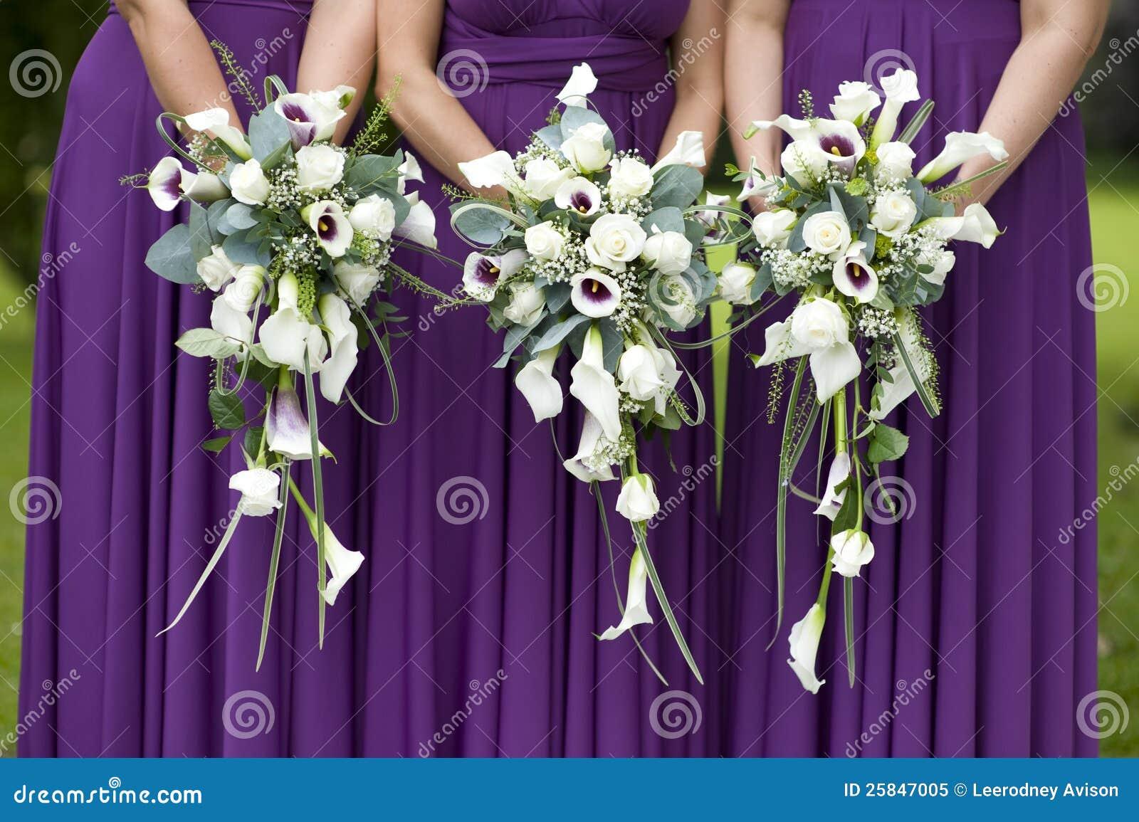 Drei Brautjunfern, die Hochzeitsblumensträuße anhalten