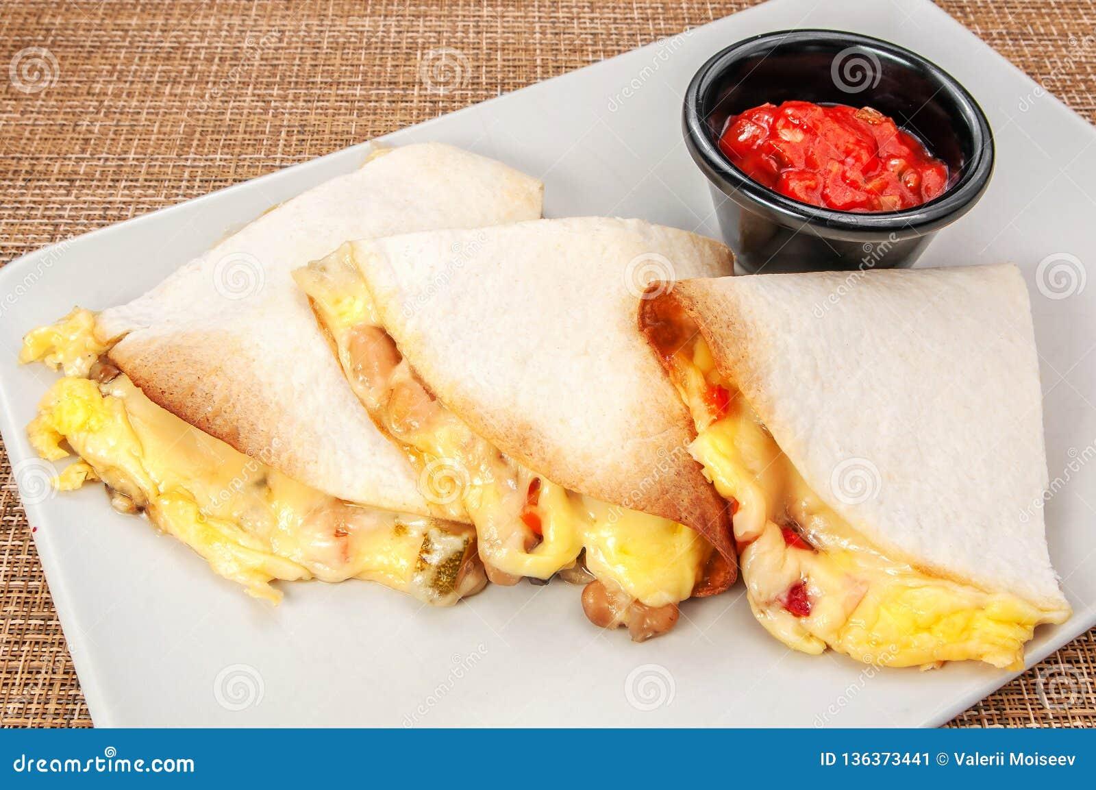 Drei Burrito Burritosverpackungen mit Rindfleisch und Gemüse auf weißer Platte mit roter Soße