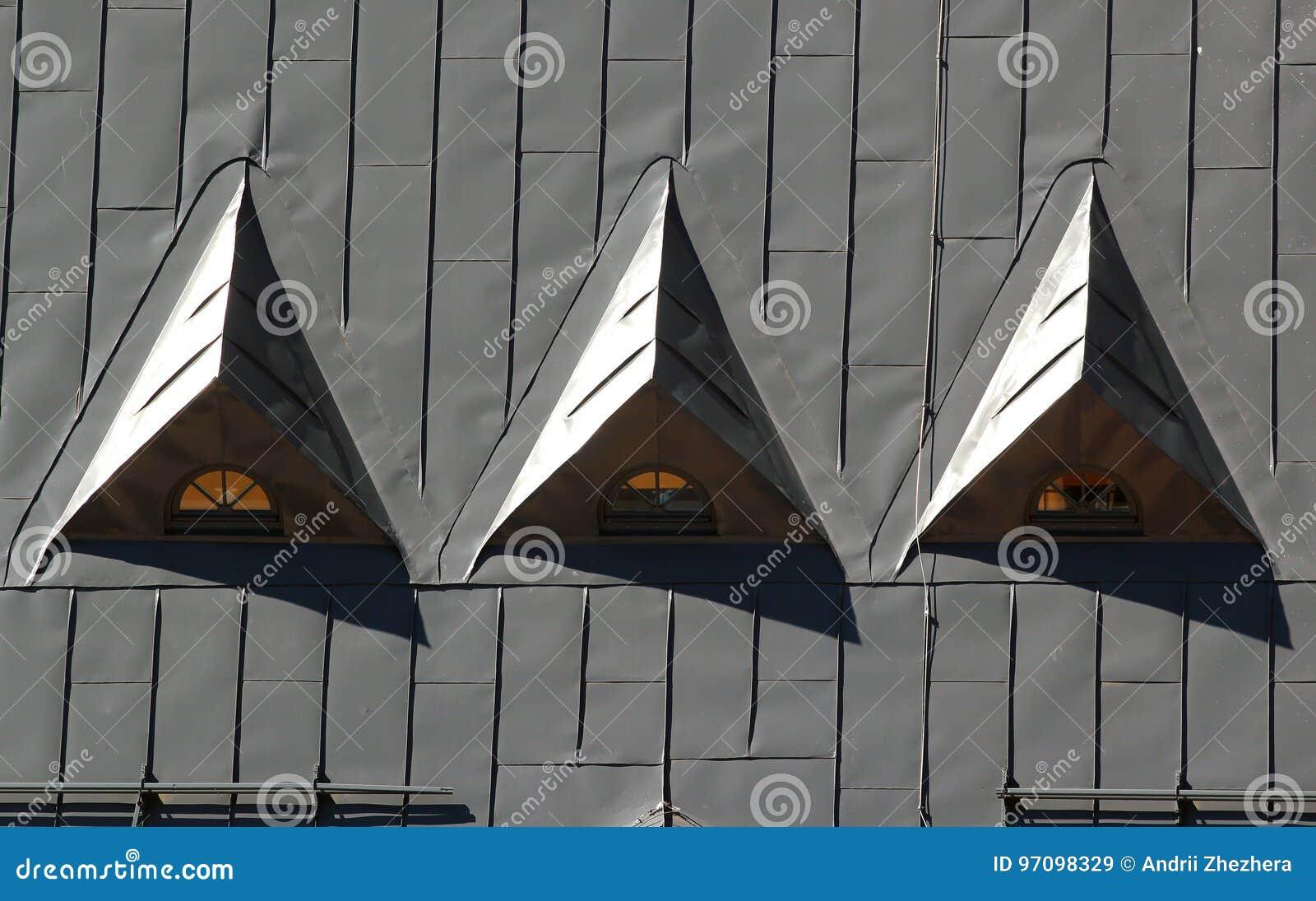 drei dreieckige dachbodenfenster in einem metalldach stockbild