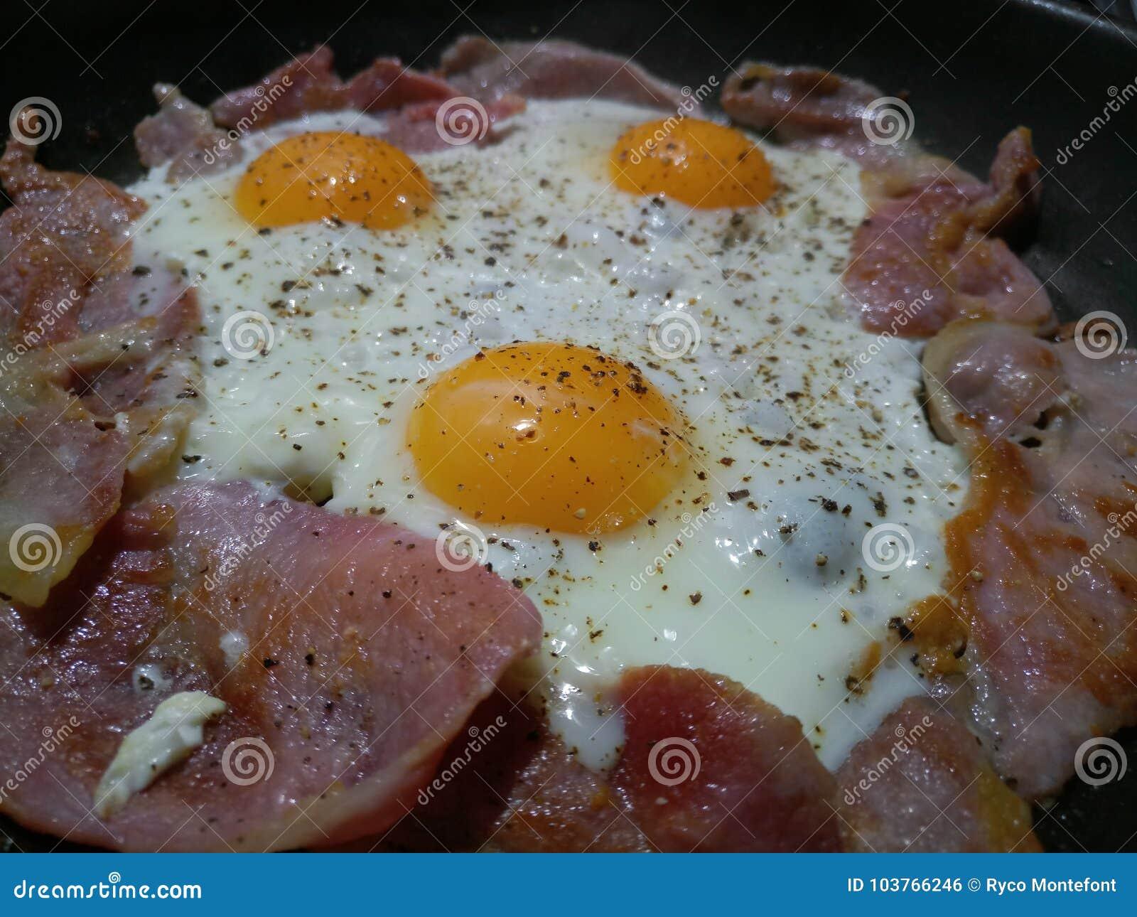 Drei Eier, die in einer heißen Wanne mit Speck sprudeln