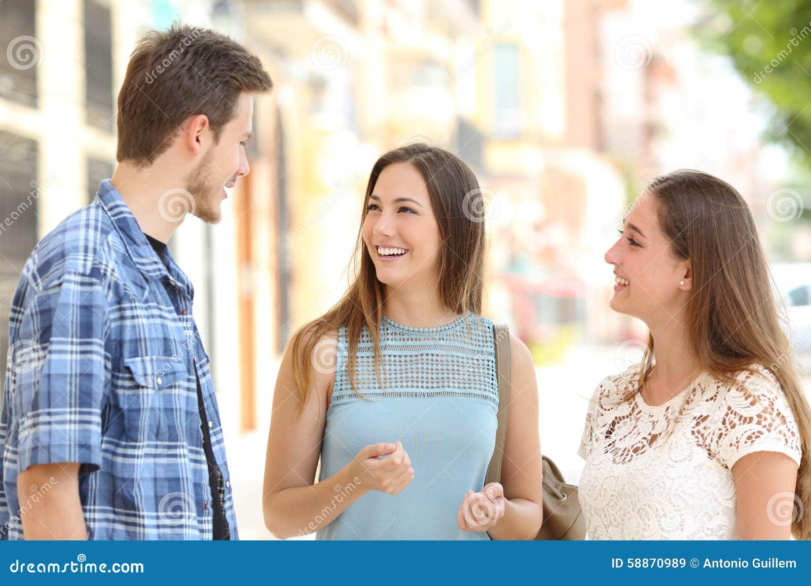 Drei Freunde, die ein Gespräch auf der Straße nehmend sprechen