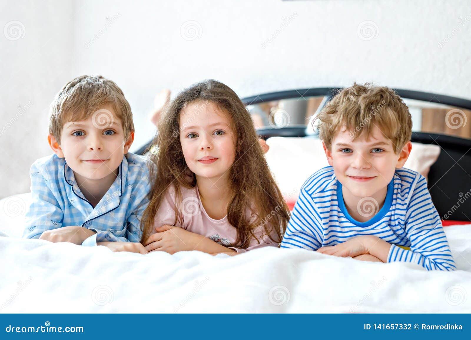 Drei glückliche Kinder in den Pyjamas Pyjamapartei feiernd Vorschule und Schuljungen und -mädchen, die Spaß zusammen haben Kinder