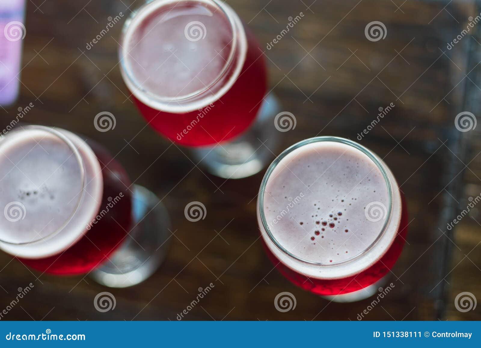 Drei Gläser mit Rotwein auf einem Holztisch Gläser Kirschbier sind- auf dem Tisch Es gibt niemand im Rahmen