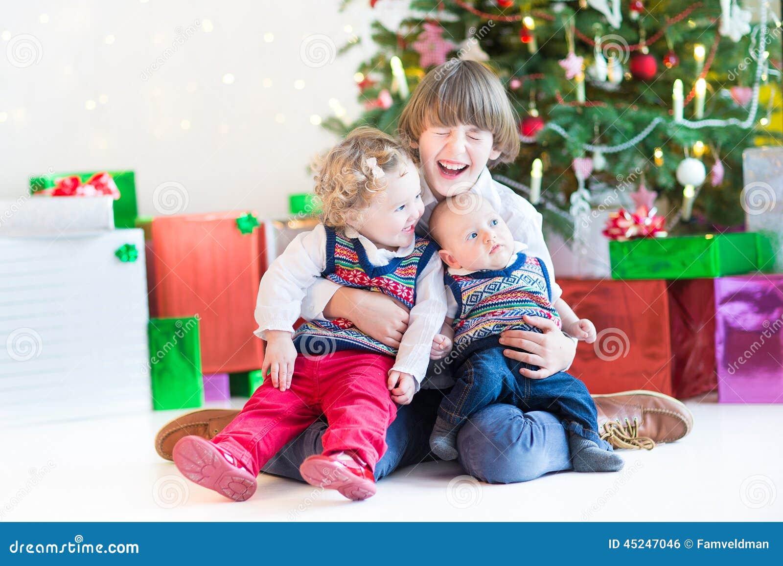 Drei glückliche Kinder - Jugendlichjunge, Kleinkindmädchen und ihr neugeborener Babybruder - zusammen spielend unter Weihnachtsba