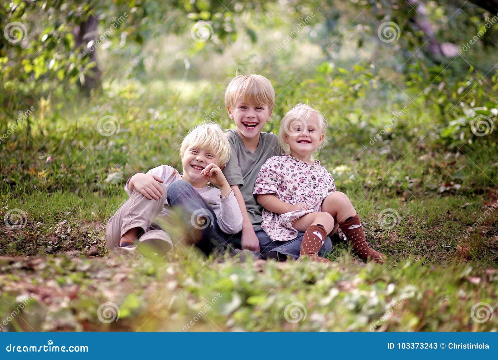 Drei glückliche Kleinkinder, die draußen lachen