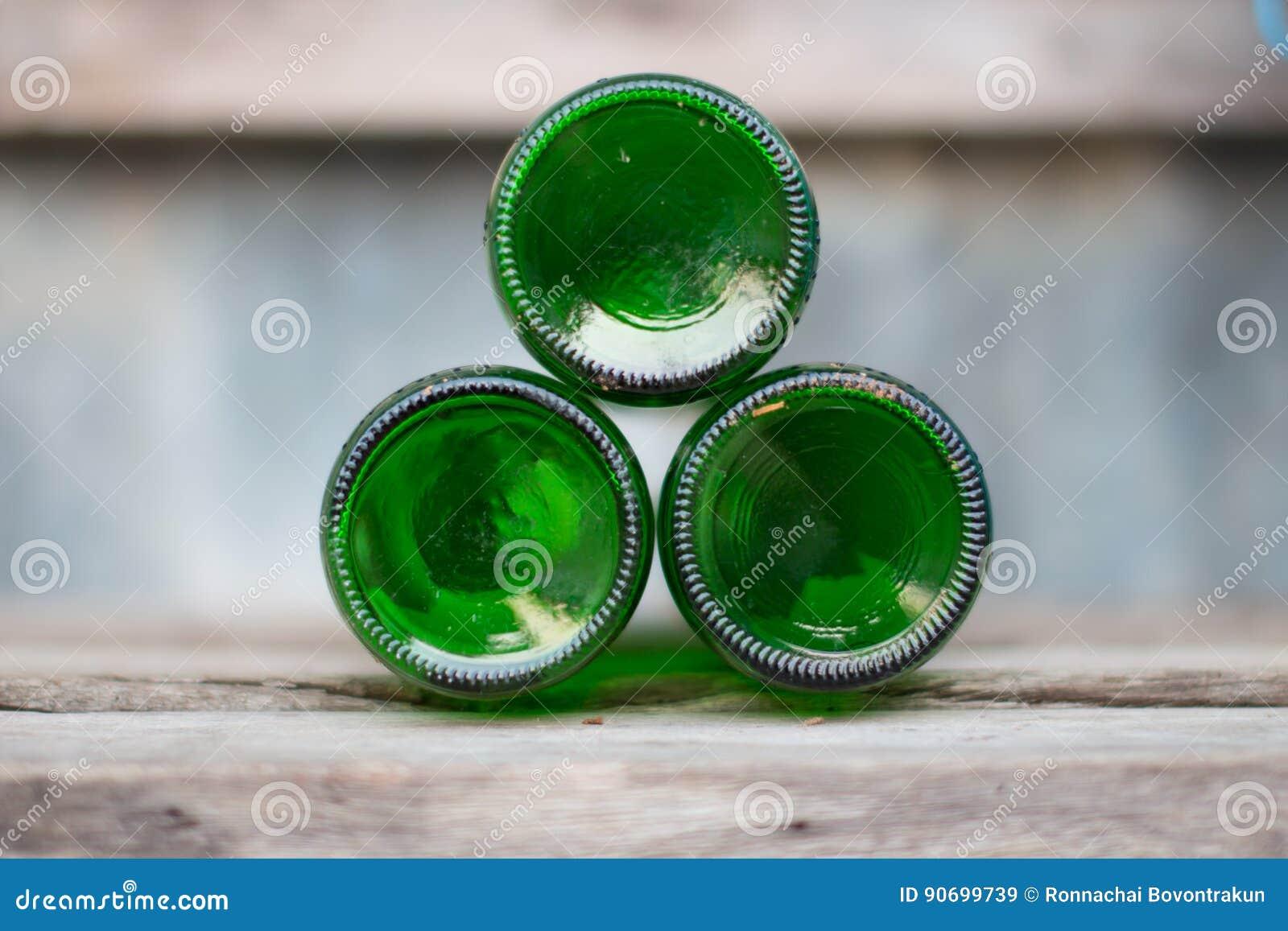 Drei Glasflaschen, grüne Unterseiten liegen voran auf hölzernem