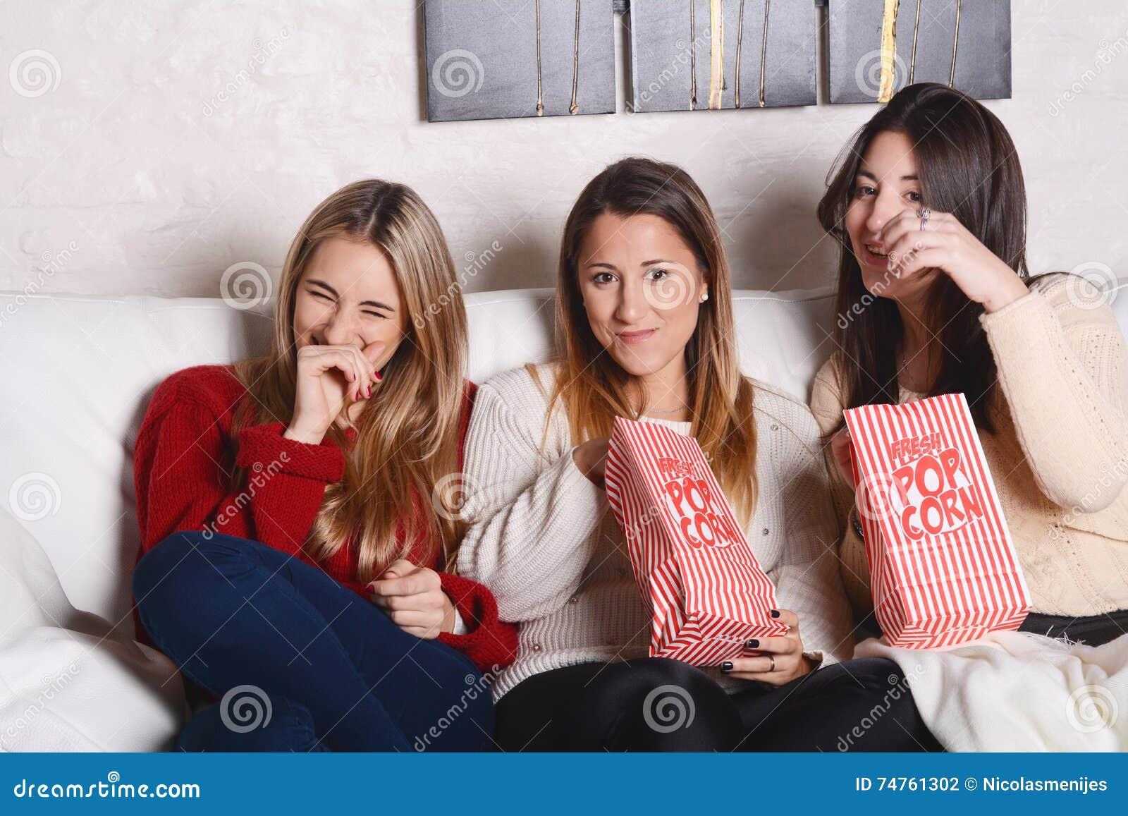 Drei junge Freunde, die Popcorn essen und Filme aufpassen