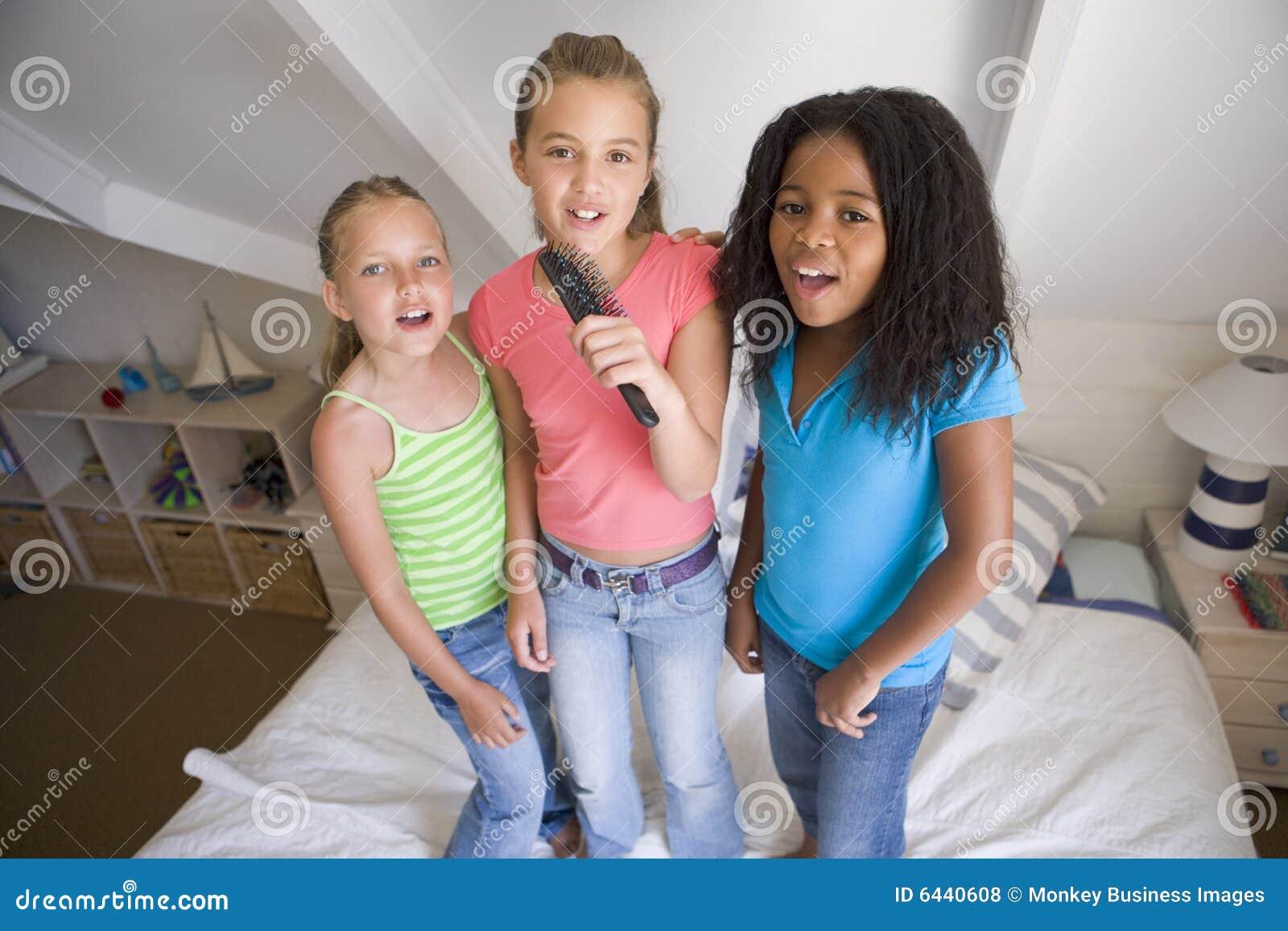 drei junge m dchen die auf einem bett stehen stockfoto bild von kind nachgemacht 6440608. Black Bedroom Furniture Sets. Home Design Ideas