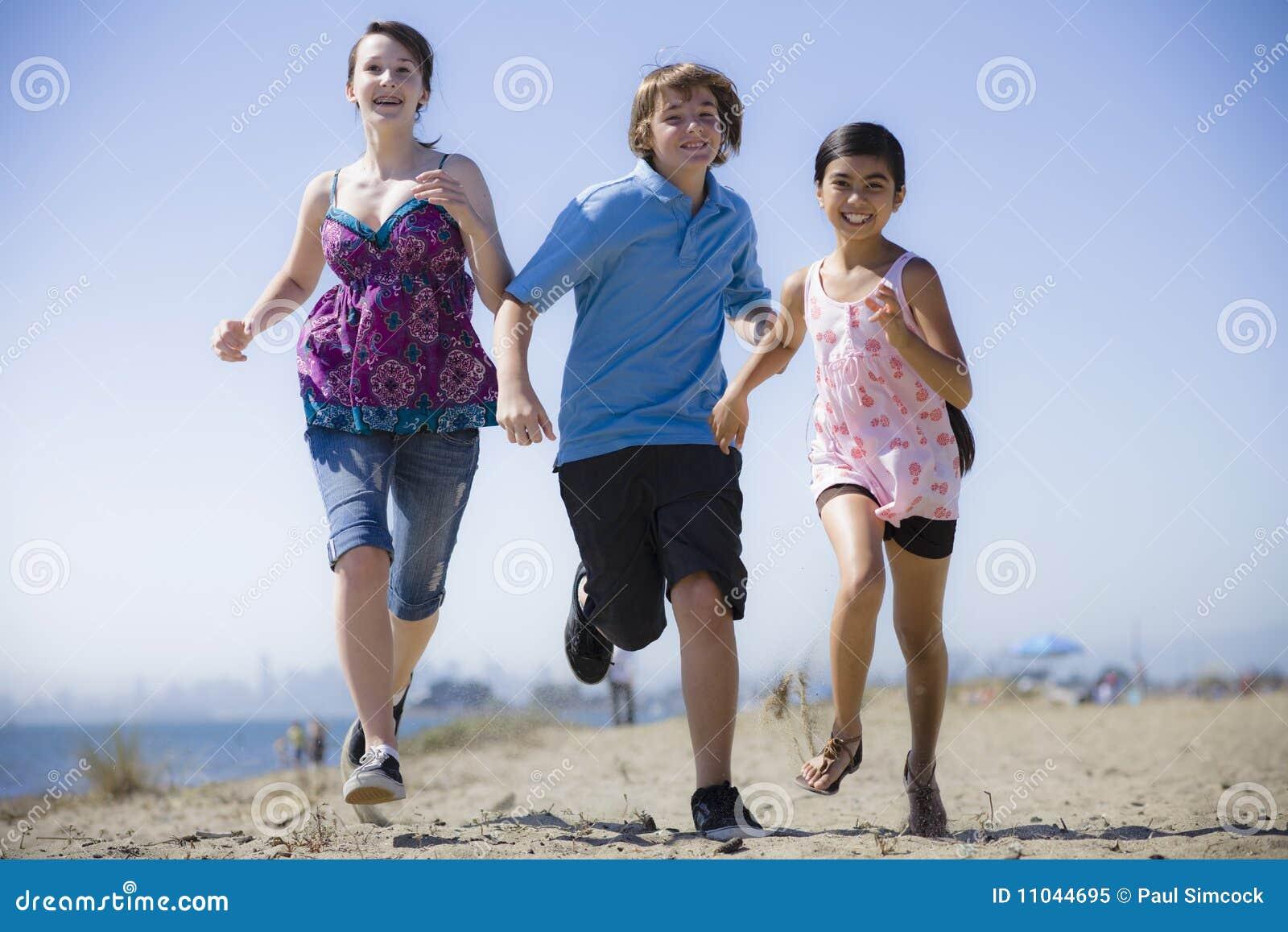 Drei Kinder, die auf Strand laufen