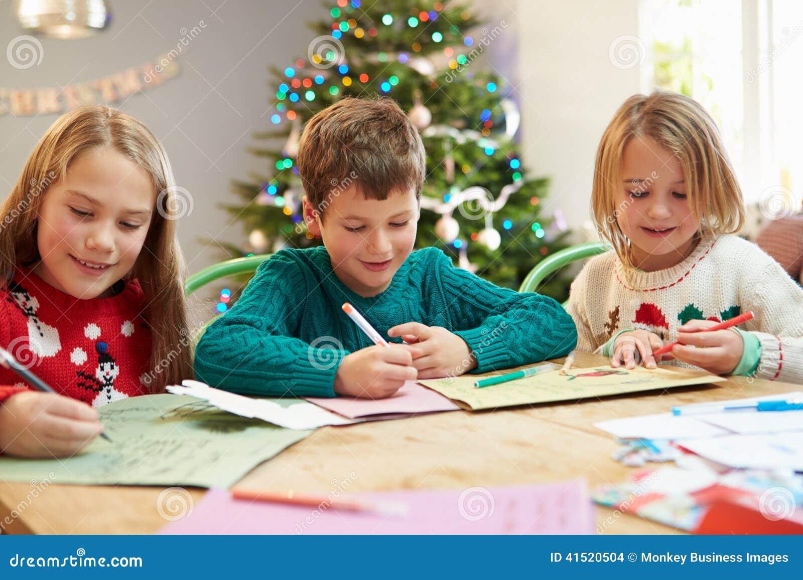 Kinderbriefe Schreiben : Drei kinder die santa together briefe schreiben stockfoto
