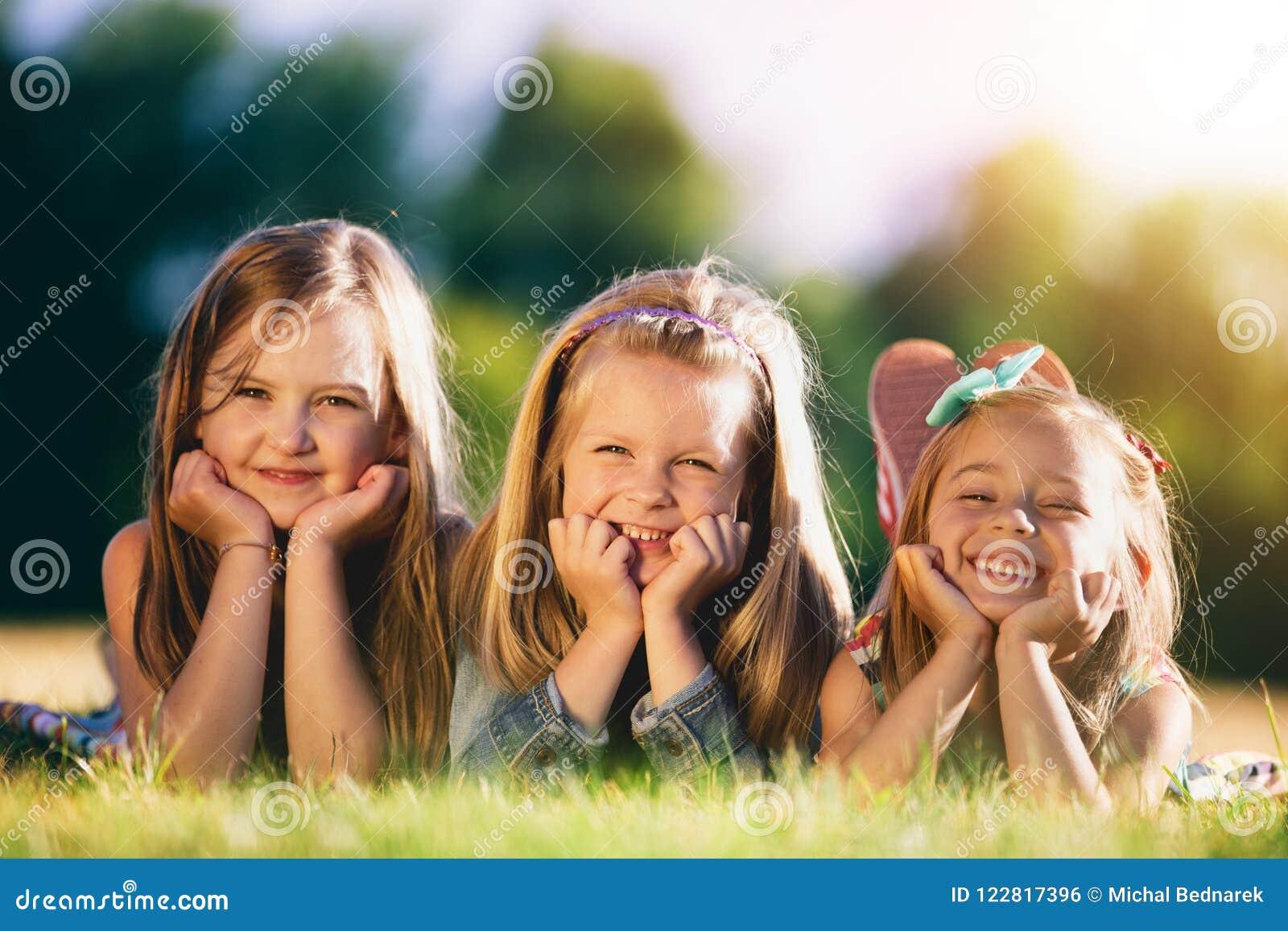 Drei lächelnde kleine Mädchen, die auf das Gras im Park legen