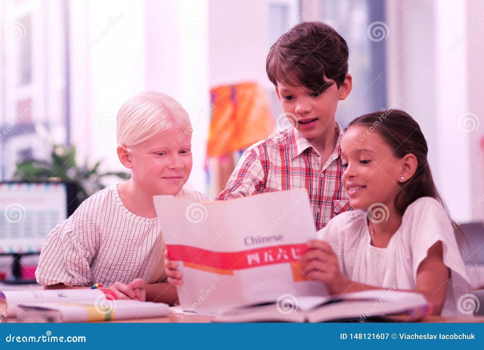 Drei lächelnde Schulkinder, die chinesisches Arbeitsbuch betrachten