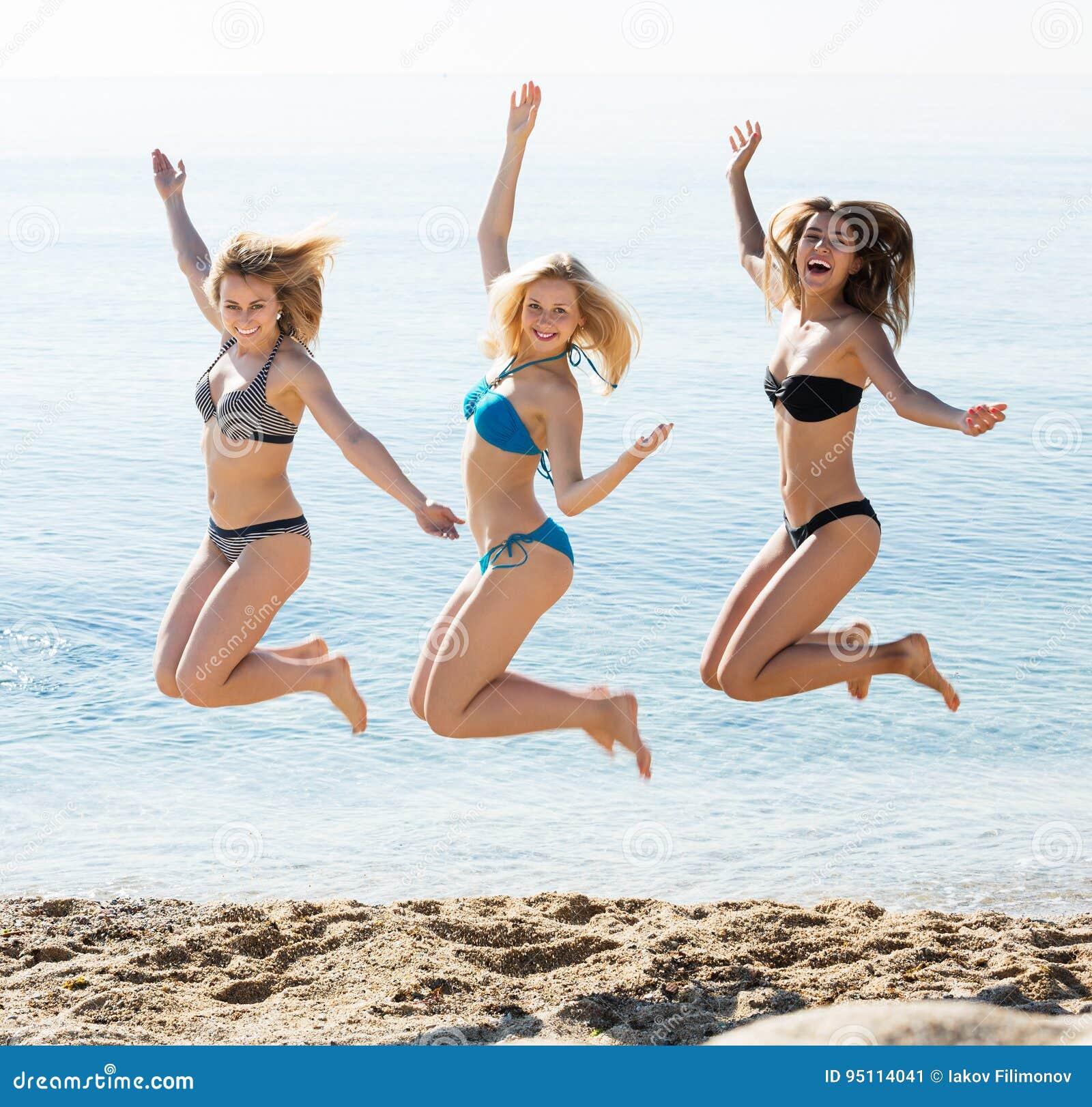 Drei Mädchen, die auf Strand springen