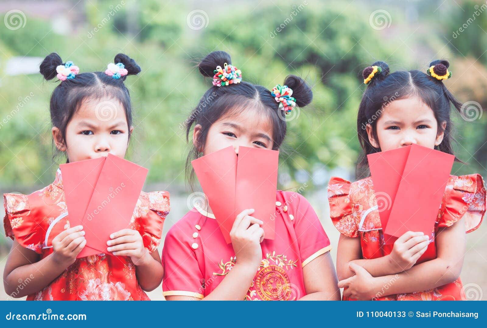 Drei nette asiatische Kindermädchen, die roten Umschlag halten