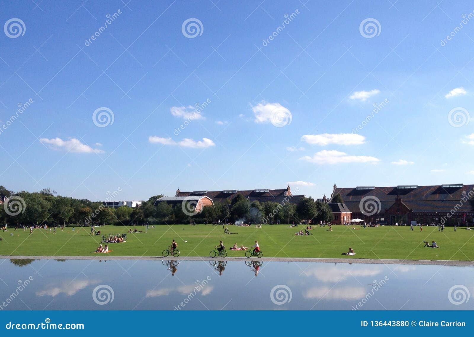 Drei Radfahrer, die in eine einzelne Datei nah an Wasser im Westerpark, mit dem Westergasfabriek im Hintergrund radfahren Amsterd