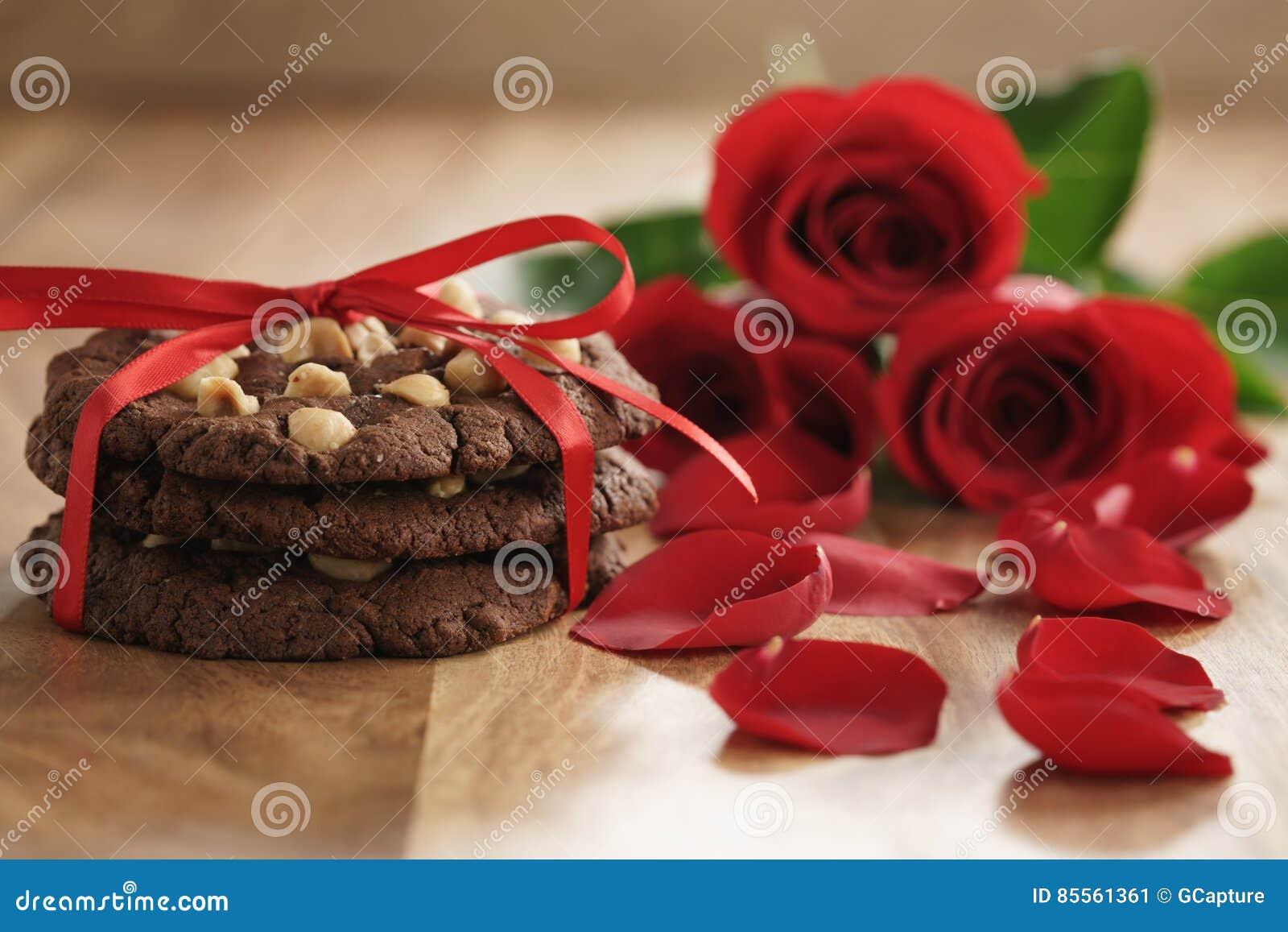 Drei rote Rosen mit selbst gemachten Schokoladenplätzchen auf alter hölzerner Tabellennahaufnahme