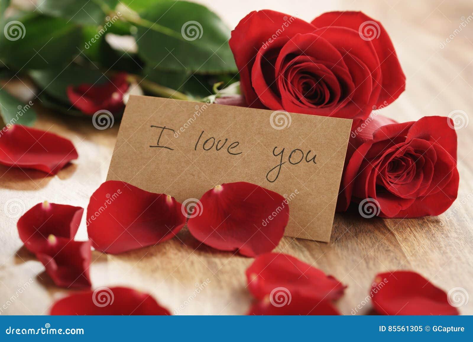 Drei rote Rosen und Blumenblätter auf alter hölzerner Tabelle mit ich liebe dich Papierkarte