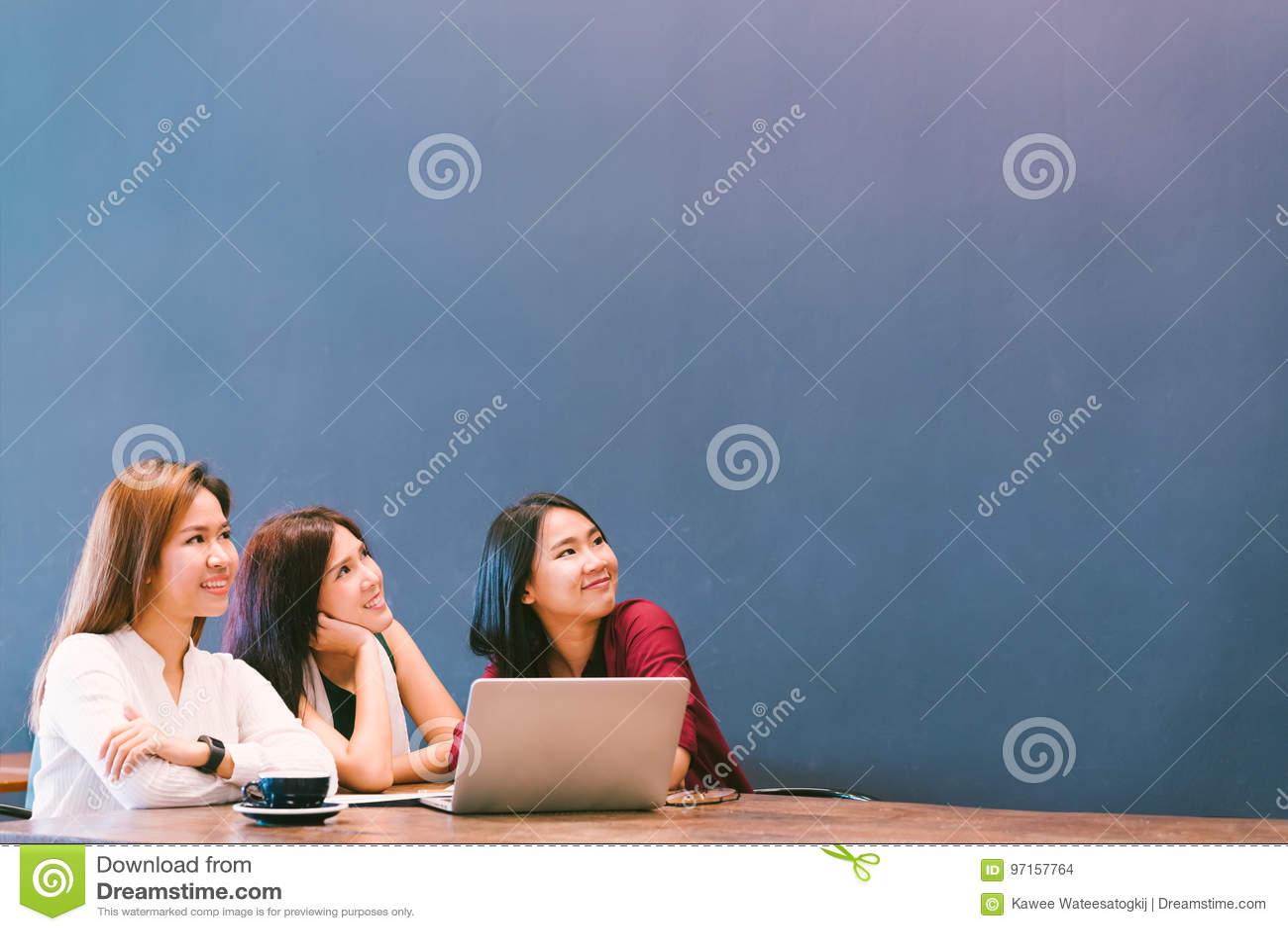 Drei schöne asiatische Mädchen, die aufwärts schauen, um Raum beim Arbeiten zu kopieren am Café, moderner Lebensstil mit Gerättec