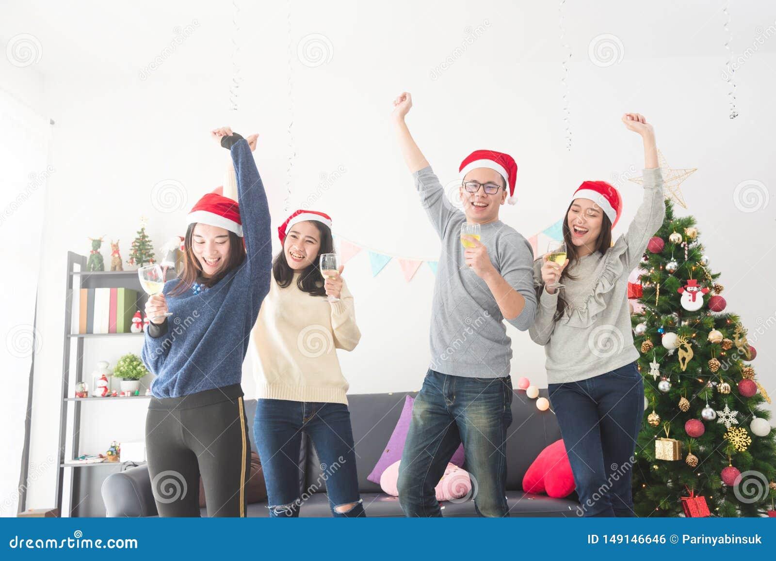 Drei schöne asiatische Mädchen und ein Mann, der Weihnachten mit Wein feiert