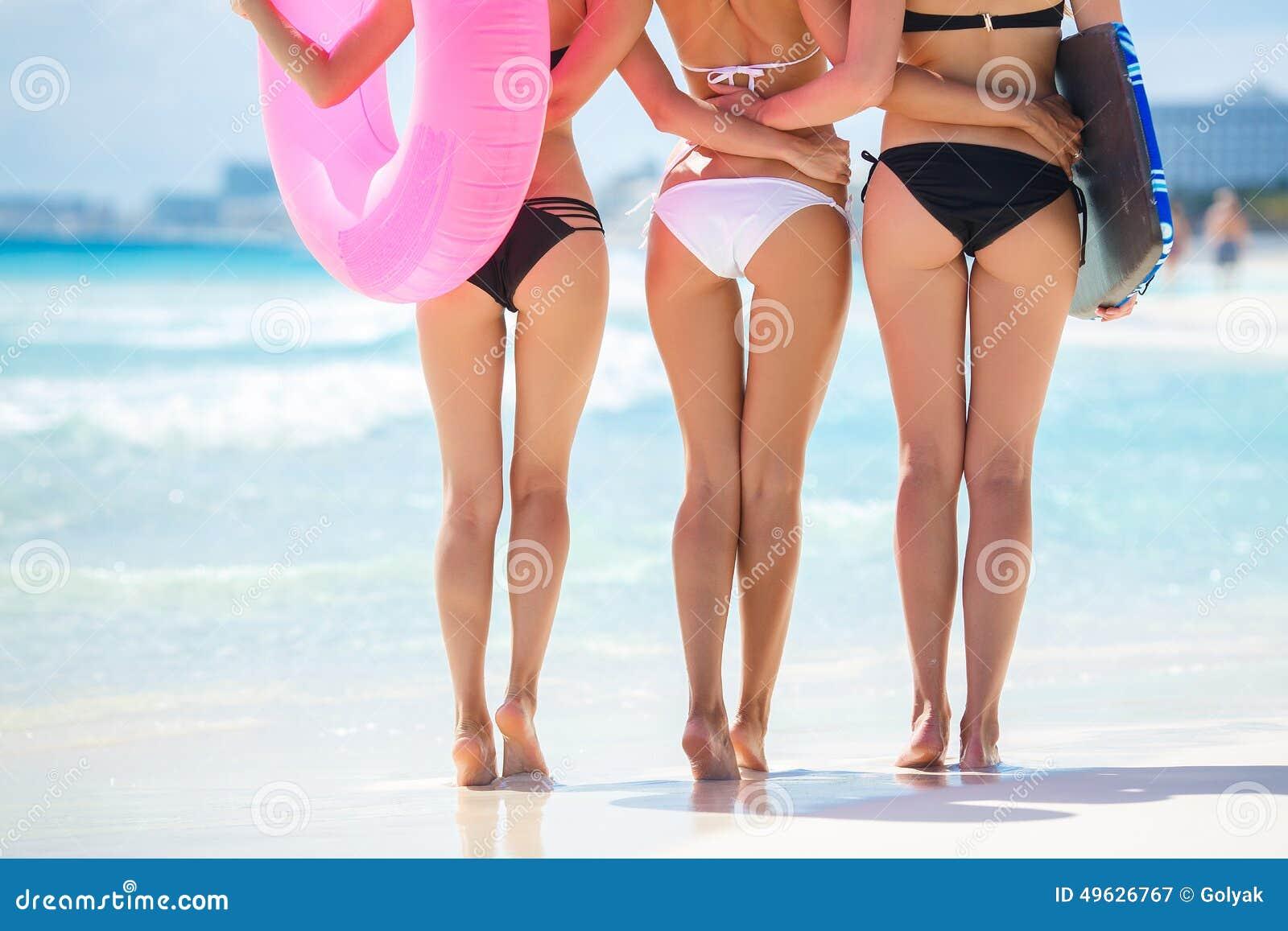 Drei schöne junge Frauen auf dem Strand in einem Bikini