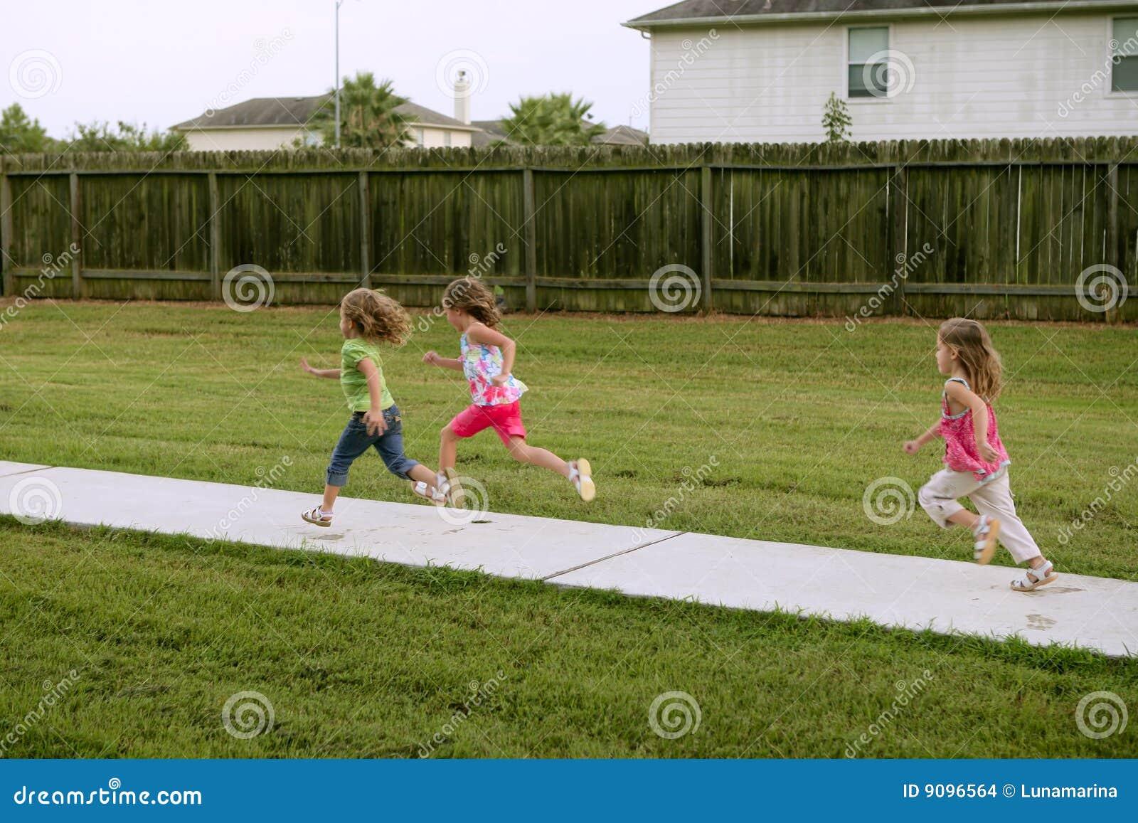 Drei Schwestermädchen, die das Laufen auf den Park spielen