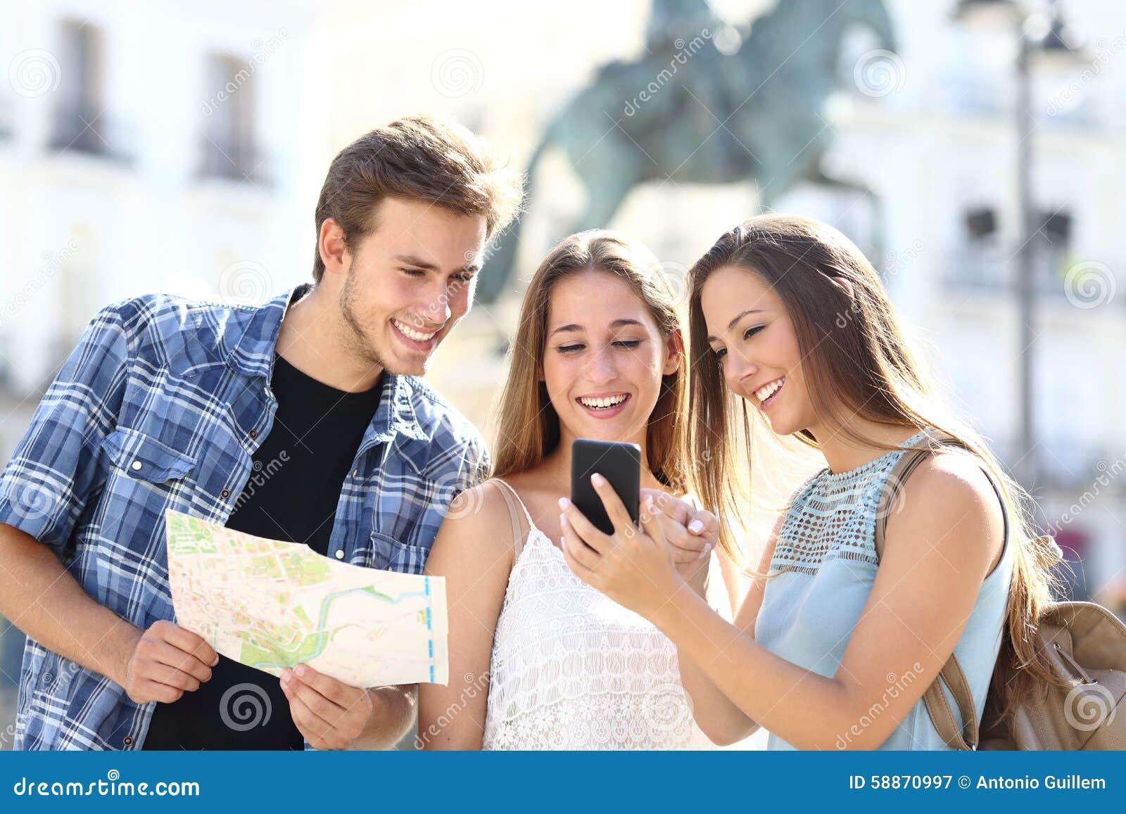 Drei touristische Freunde, die gps am intelligenten Telefon konsultieren