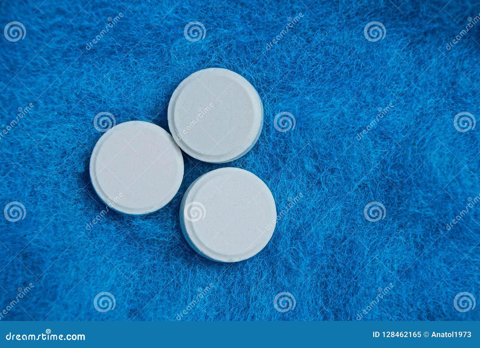 Drei weiße runde Pillen auf blauem Hintergrund des woolen Gewebes