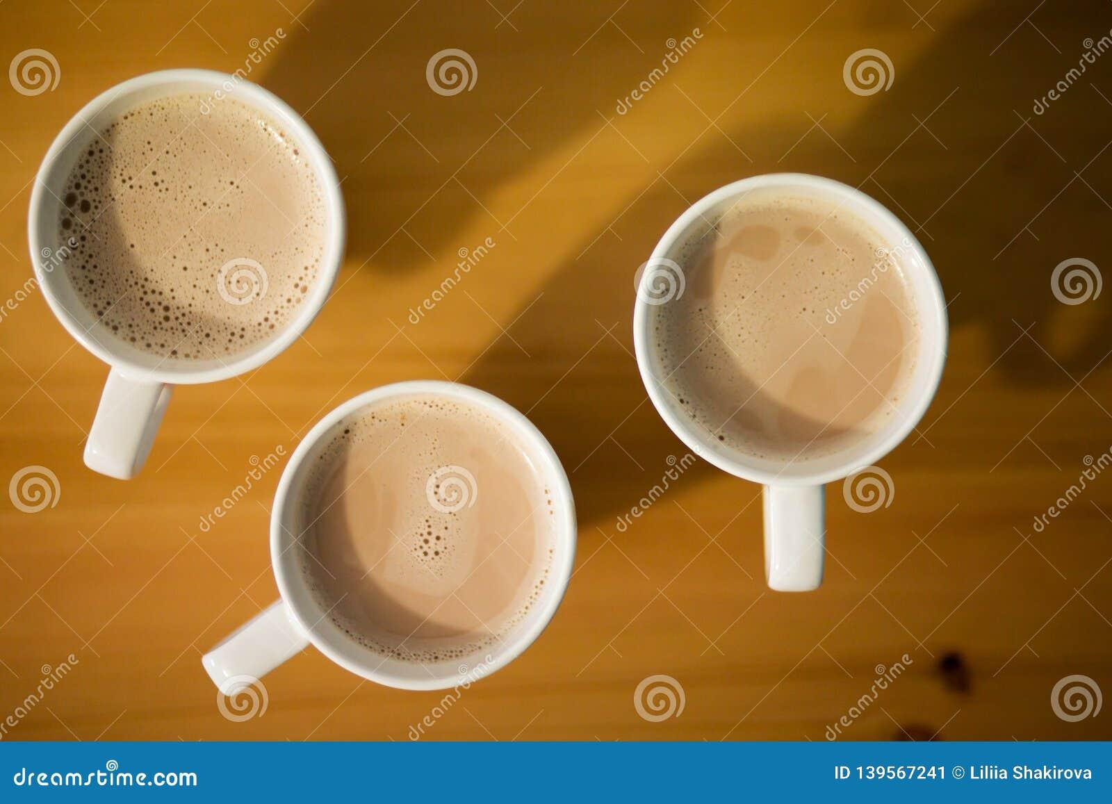Drei weiße Schale heißer Latte, Kaffee oder Kakao auf Holztisch, Draufsicht, Abschluss oben
