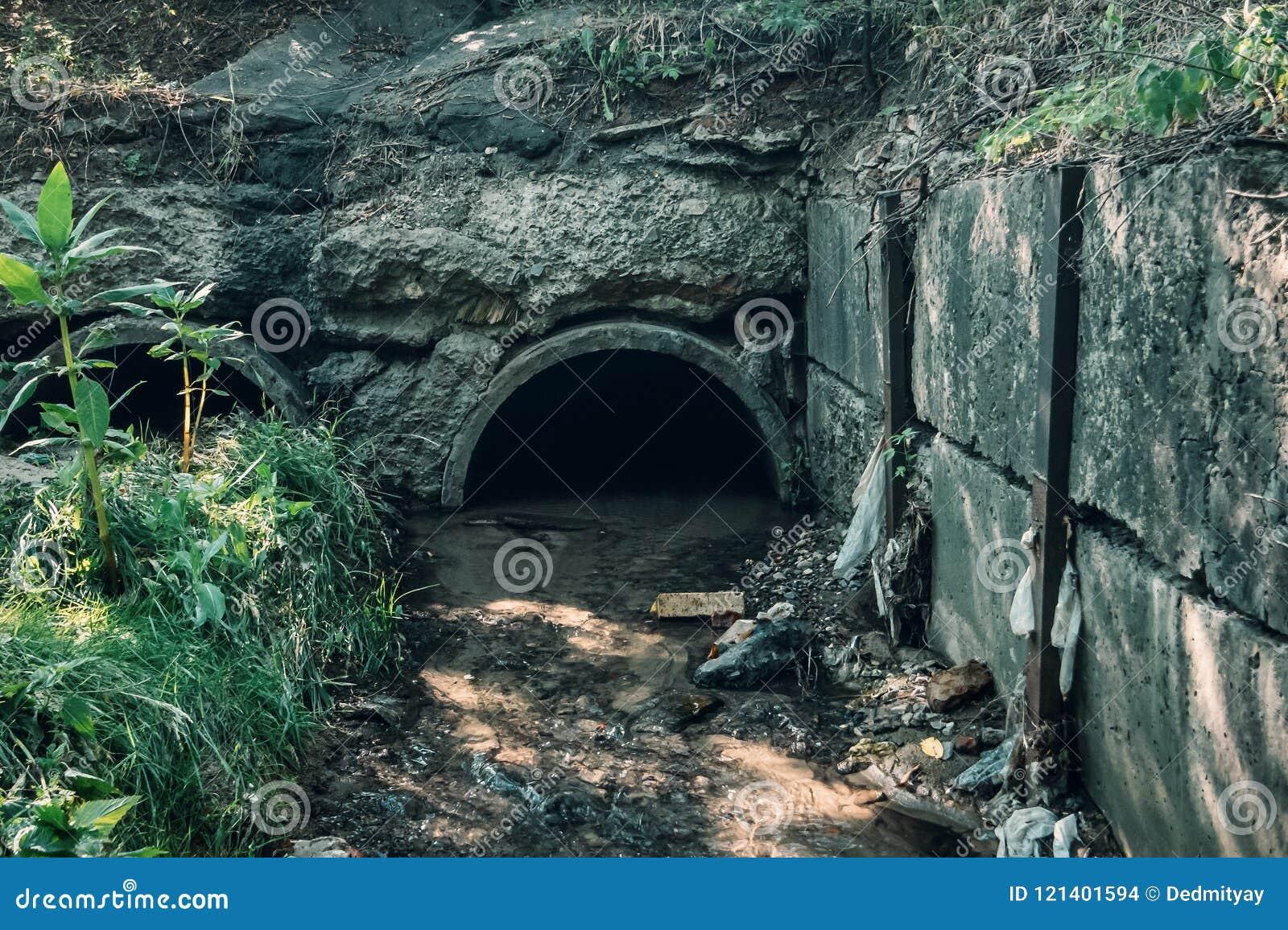 A drenagem concreta velha conduz com o tubo de fluxo das águas residuais, da água de esgoto ou do túnel do esgoto com córrego da
