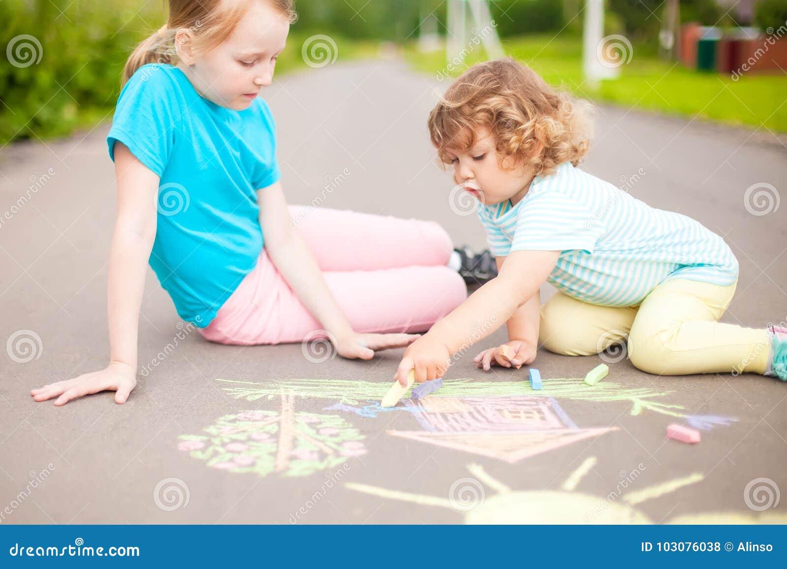 Drenaje De Las Pequeñas Hermanas Con Tiza Del Color Al Aire Libre