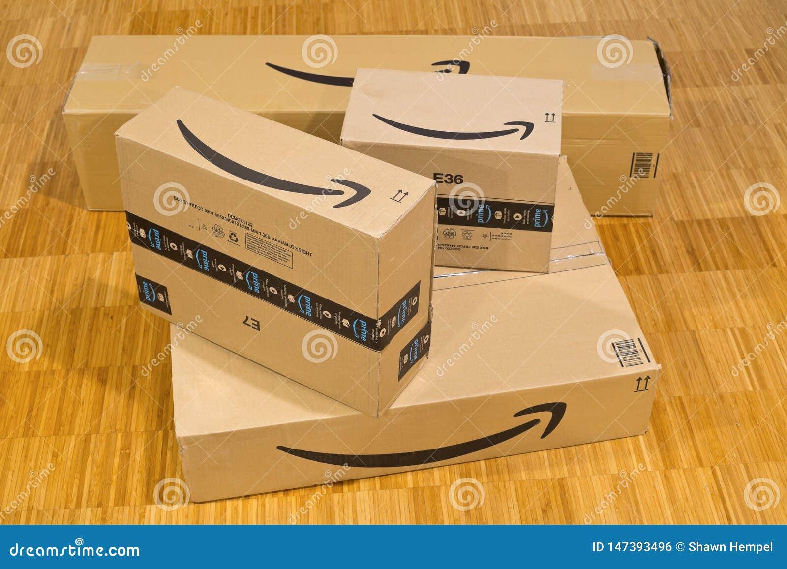 DRESDEN, ALEMANIA - 3 DE ABRIL DE 2019: Pila de paquetes del Amazon Prime en piso de madera de la oficina