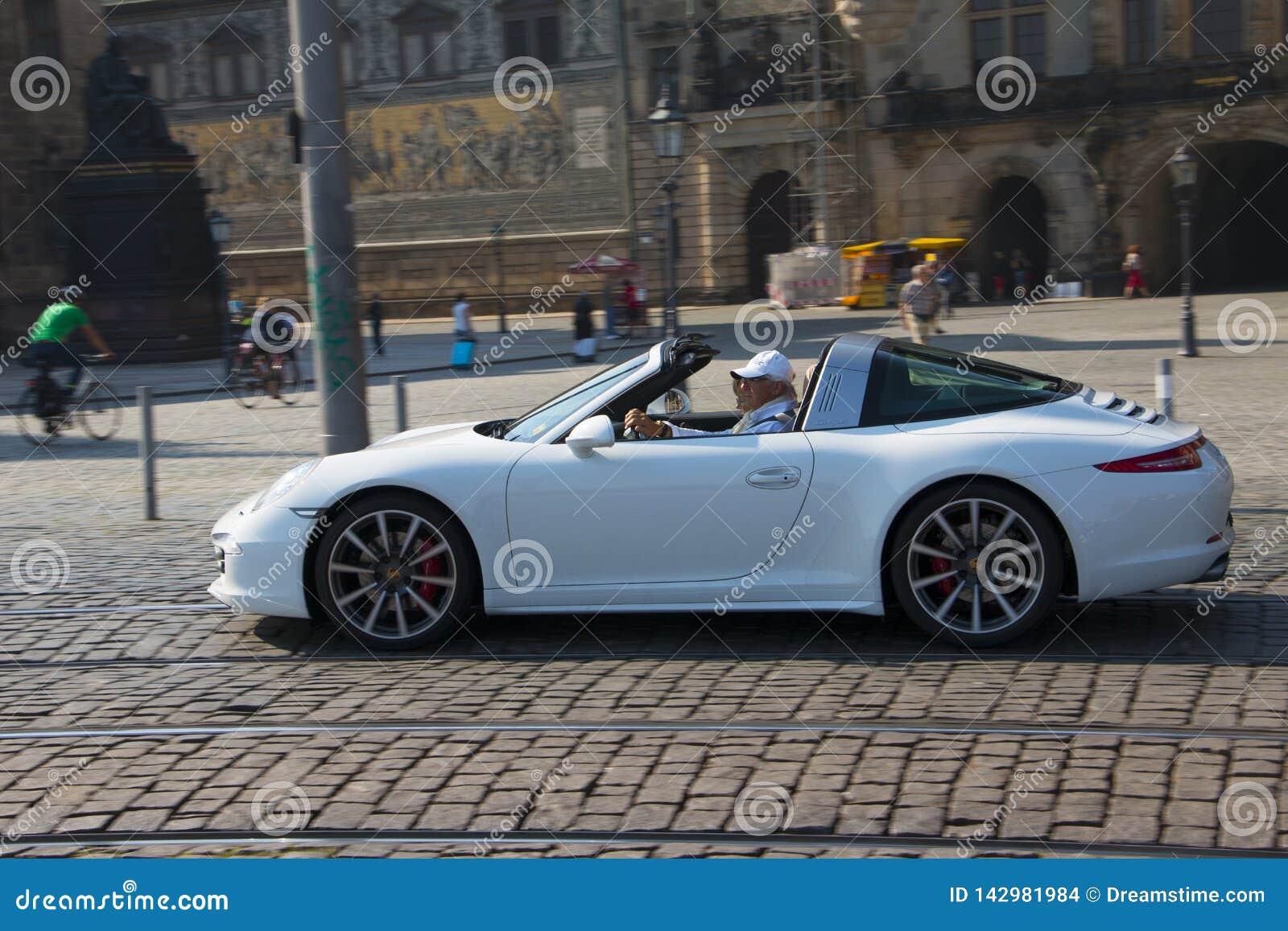 Dresden, Alemania - julio de 2015: El viejo hombre monta a su Porsche