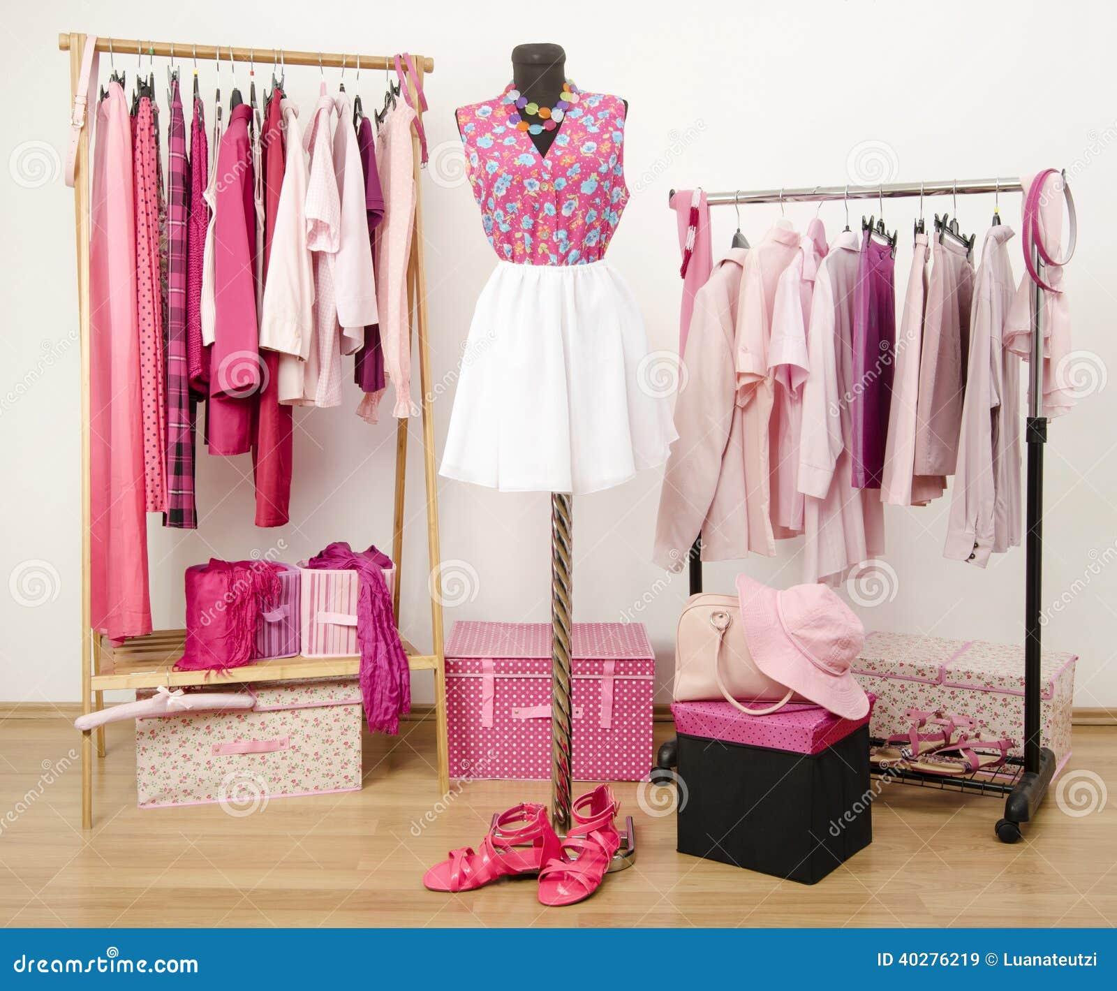 Dressinggarderoben med rosa färger beklär ordnat på hängare och en dräkt på en skyltdocka.