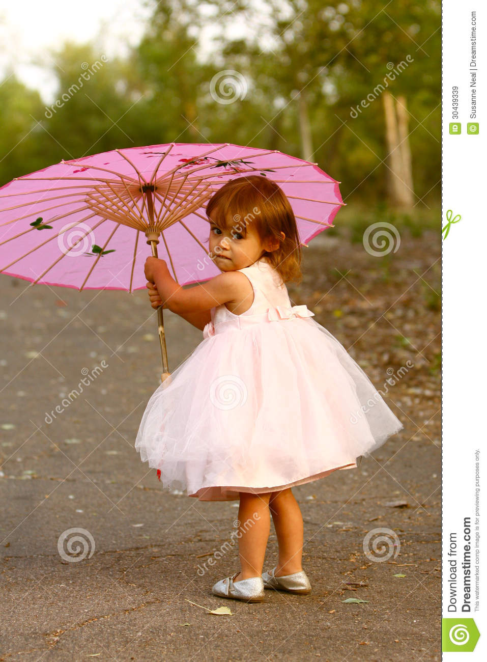 Dressy two-year-old girl carrying pink parasol