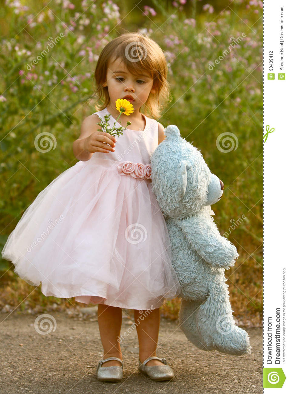 Dressy two-year-old girl in pink dress holding stuffed bear and flower