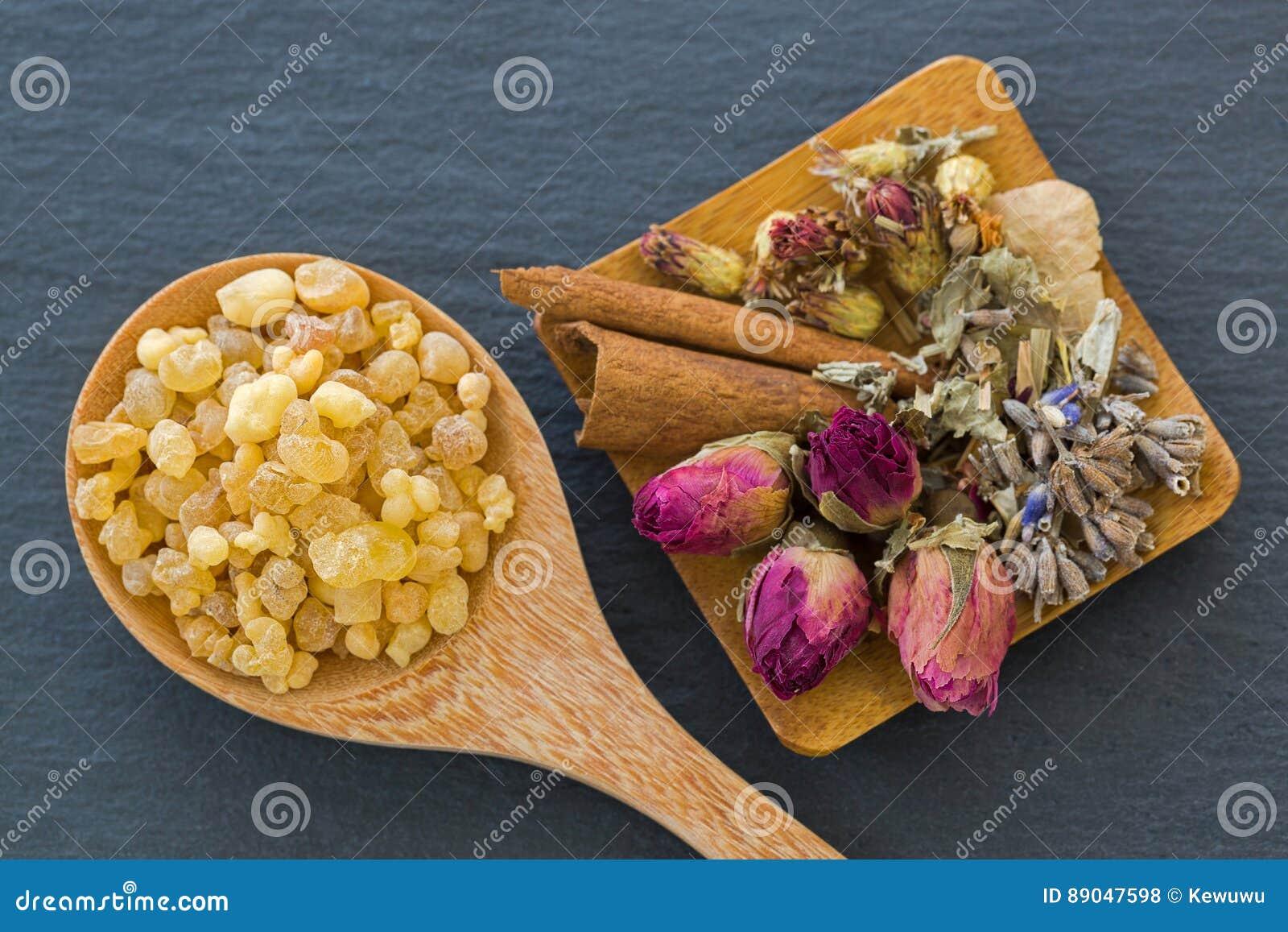 Drewniana łyżka aromatyczny żółty żywicy dziąsło obok wysuszonych kwiatów