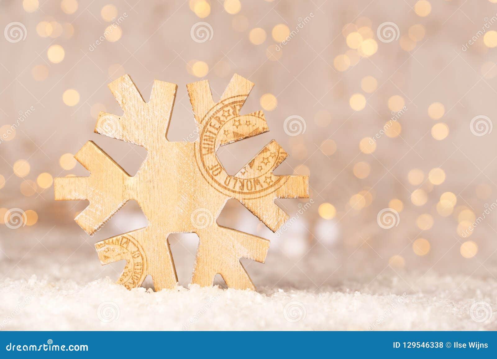 Drewniana boże narodzenie dekoracja kształtująca jako płatek śniegu z teksta światem zimy i miękkiej części bokeh żółci christmas