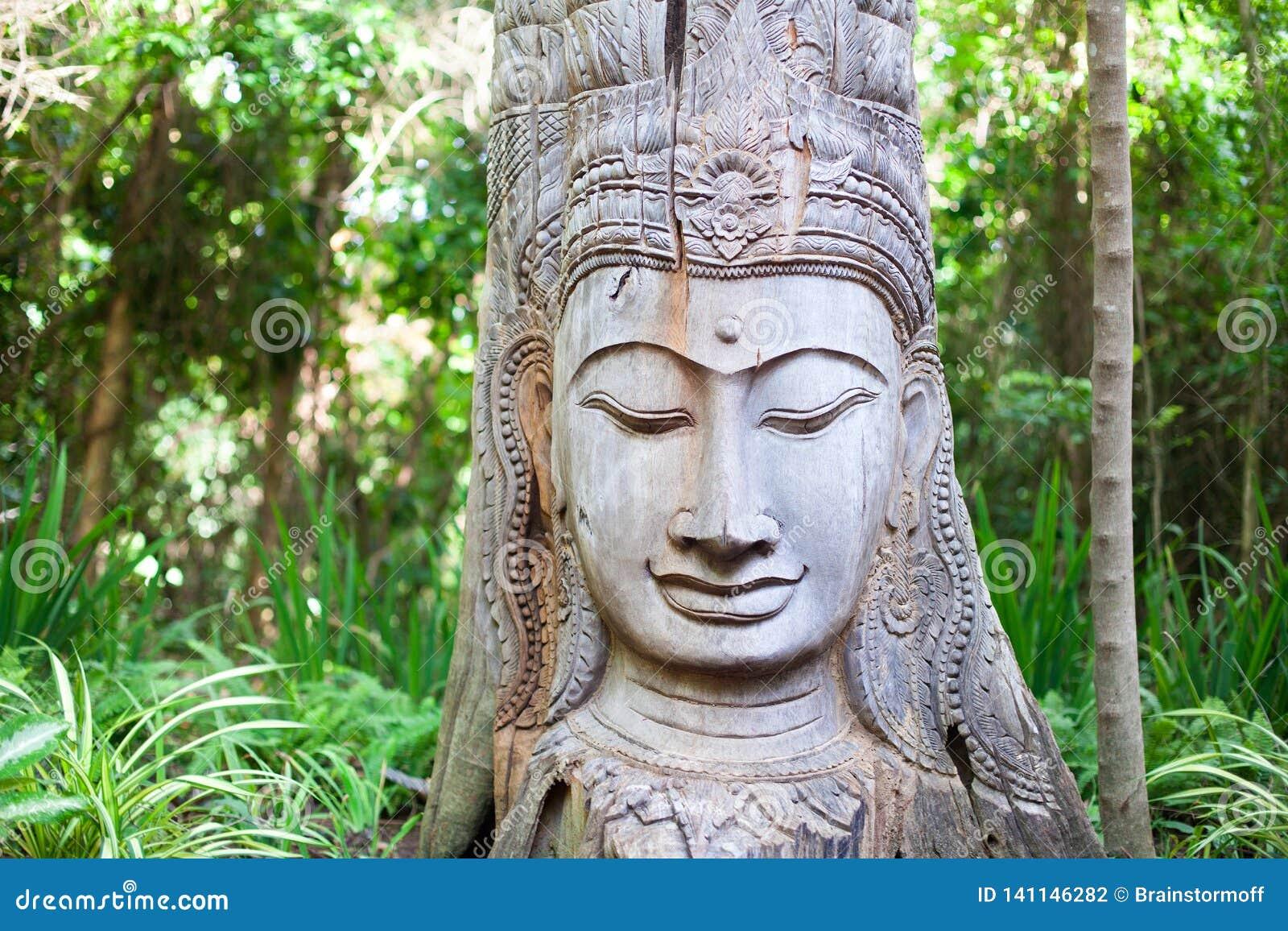 Drewniana Buddha statua na zielonym drzewa tle
