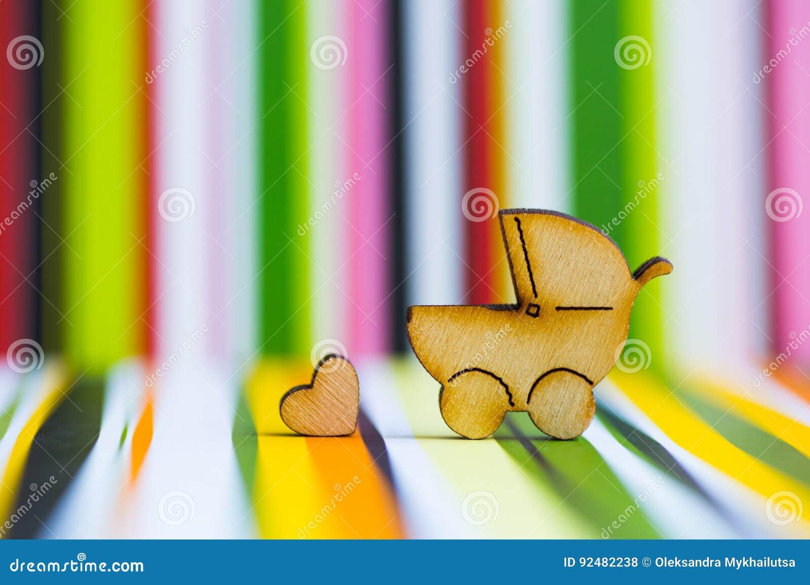 Drewniana ikona dziecko powozik i mały serce na kolorowym pasiastym b