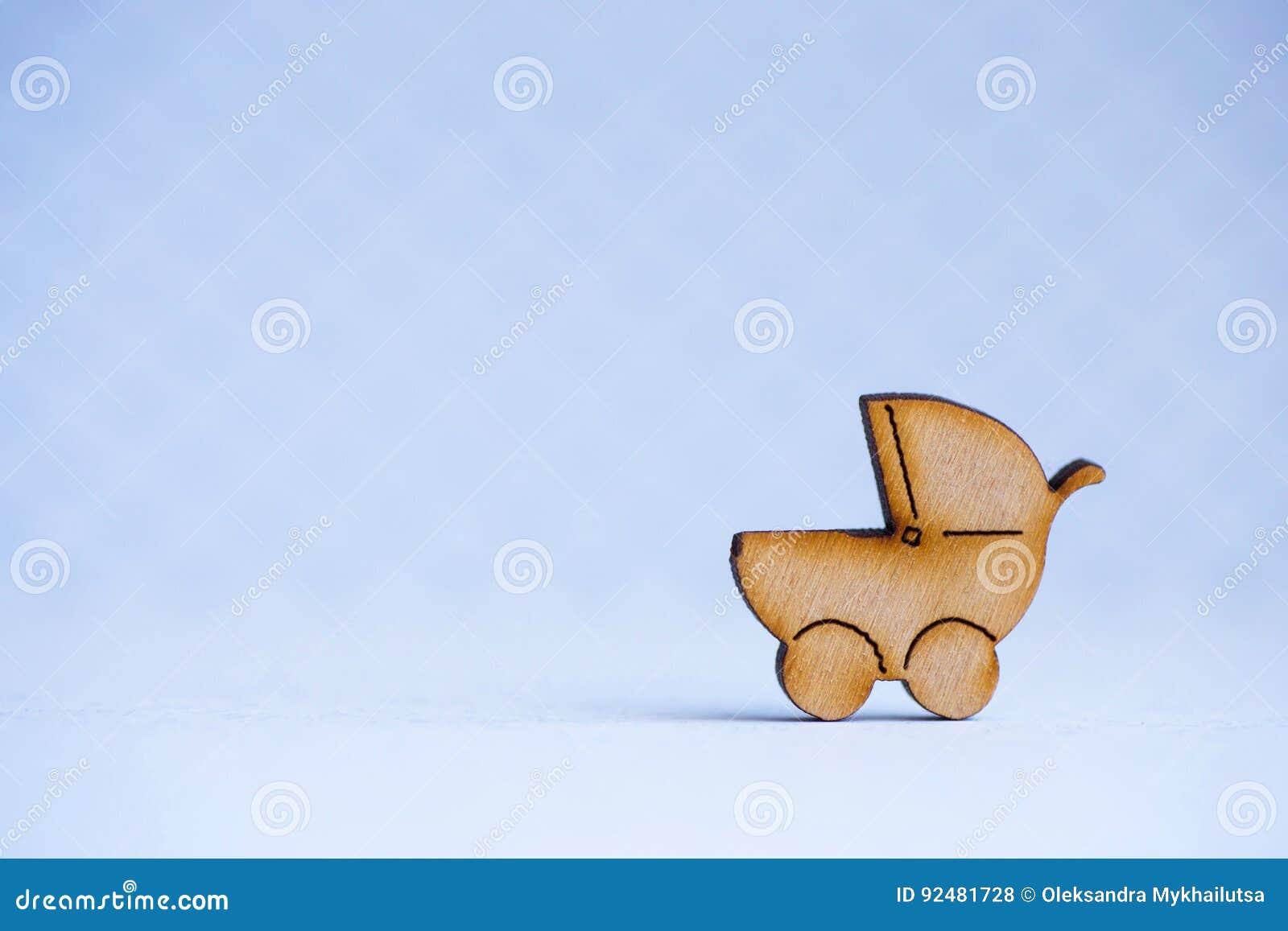Drewniana ikona dziecko powozik na szarym tle