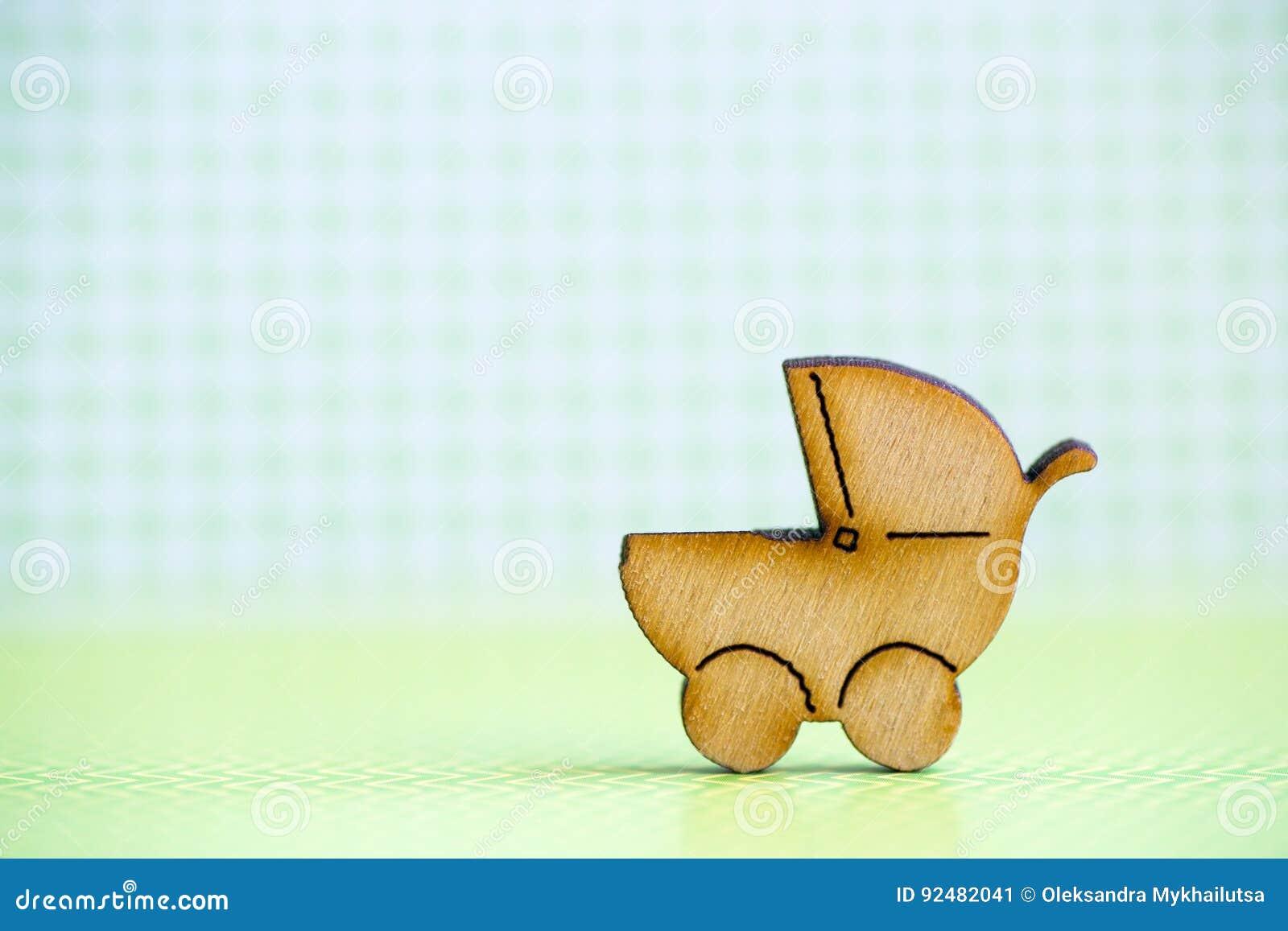 Drewniana ikona dziecko powozik na zielonym w kratkę tle