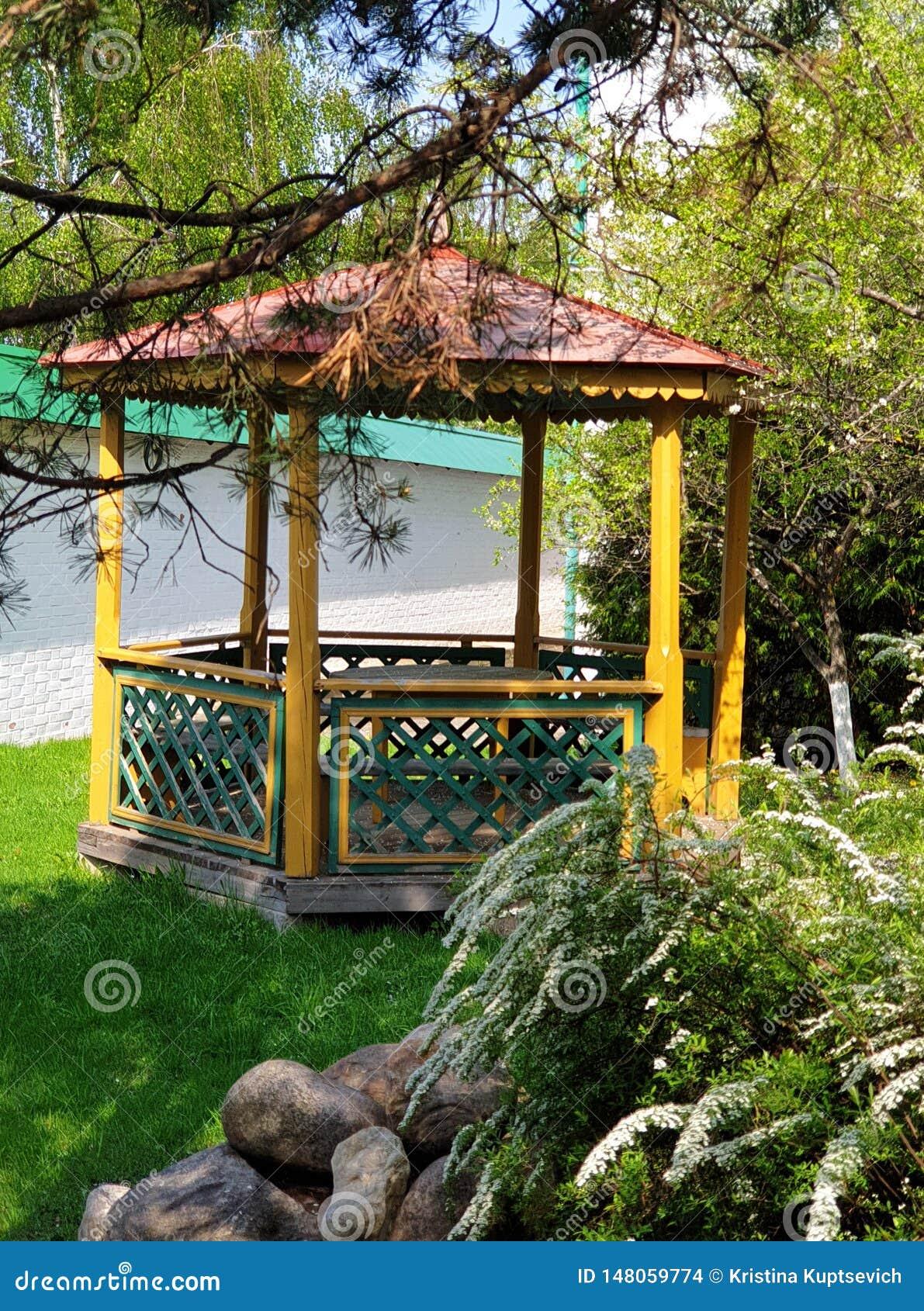 Drewniana pergola w dekoracyjnym kwitnącym wiosna ogródzie