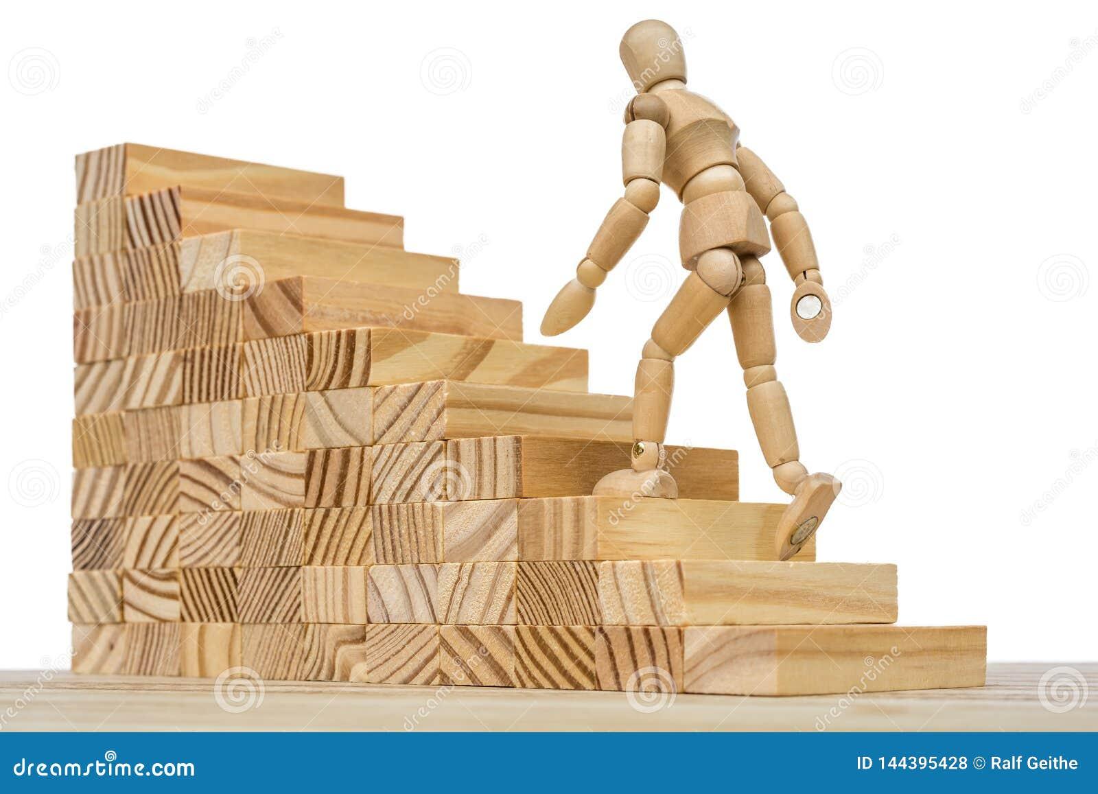 Drewniana postać biega w górę wysokich schodków jako metafora dla pracy i kariery