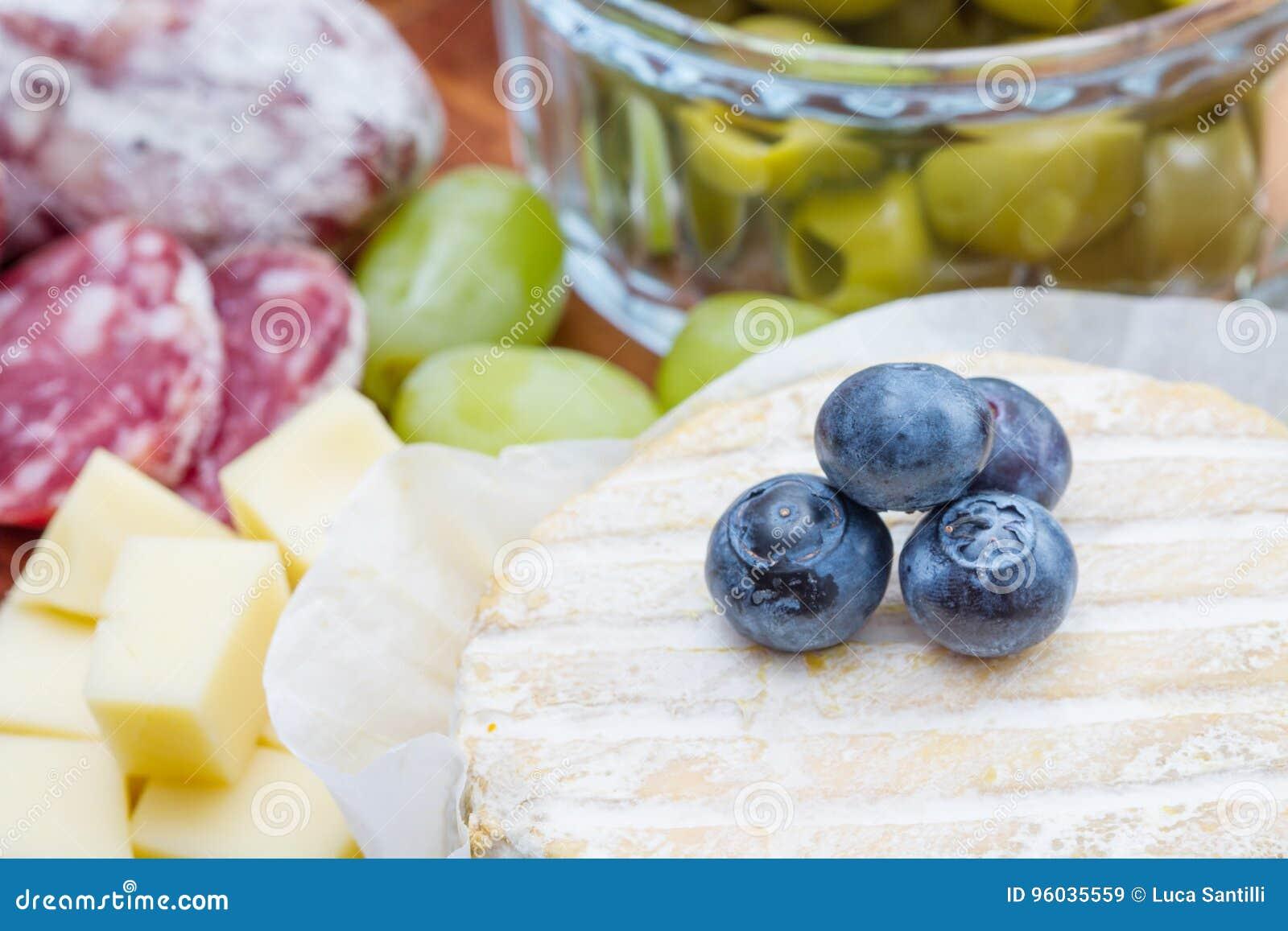 Drewniana tnąca deska z serem, zimnymi cięciami i dżemami,