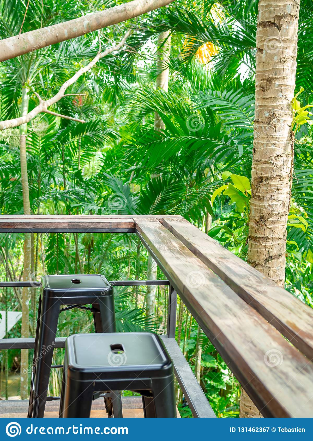 Drewnianego kontuaru prętowi i czarni metali krzesła na tarasie w lasowego tła pionowo stylu
